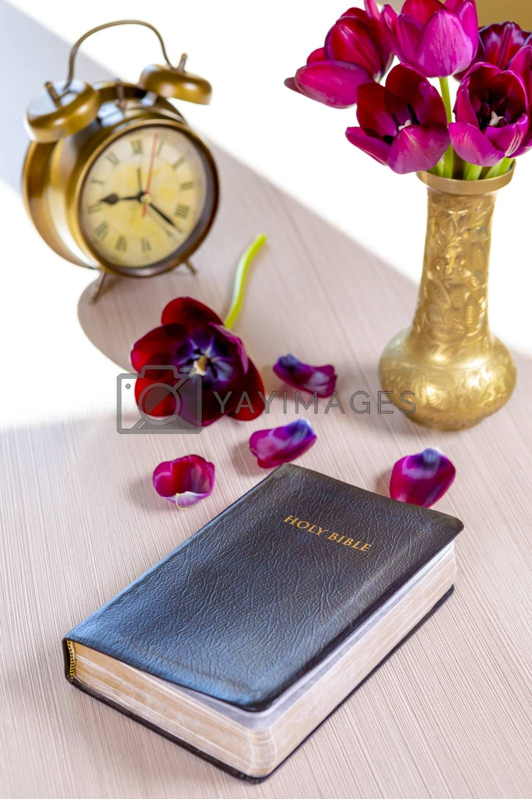 Holy Bible and old gold alarm clock with flowers on wooden table background. Time for studying, reading and spirituality concept.