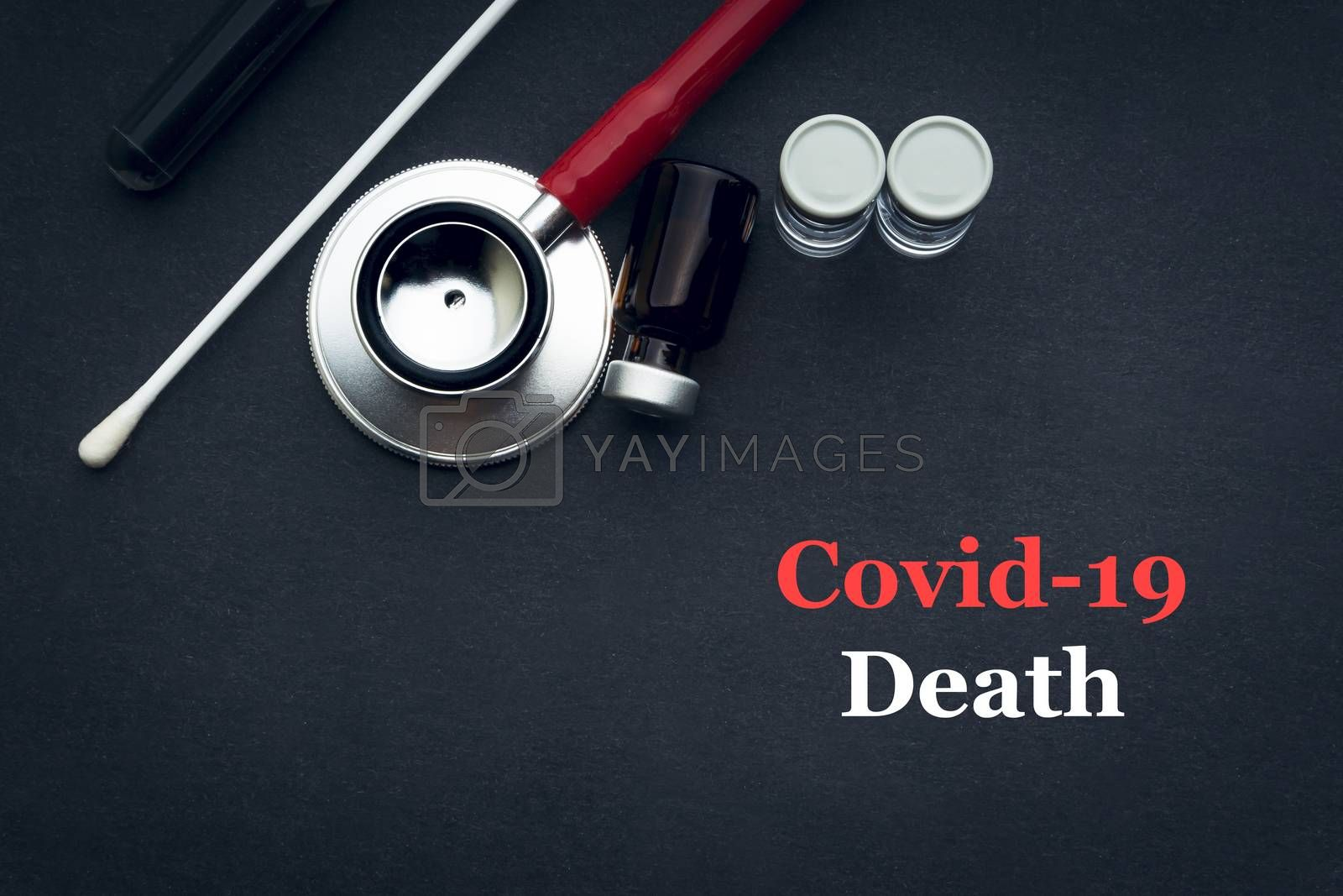 COVID-19 or CORONAVIRUS DEATH text with stethoscope, medical swab and vial on black background. Covid-19 or Coronavirus concept.