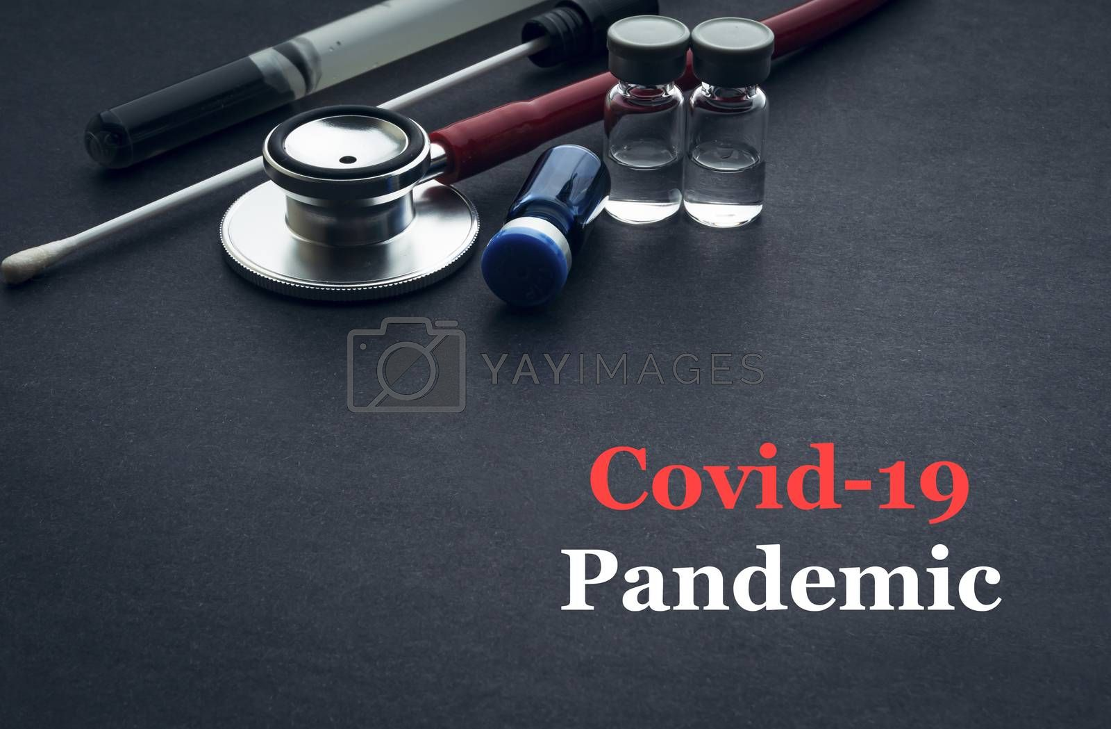 COVID-19 or CORONAVIRUS PANDEMIC text with stethoscope, medical swab and vial on black background. Covid-19 or Coronavirus concept.