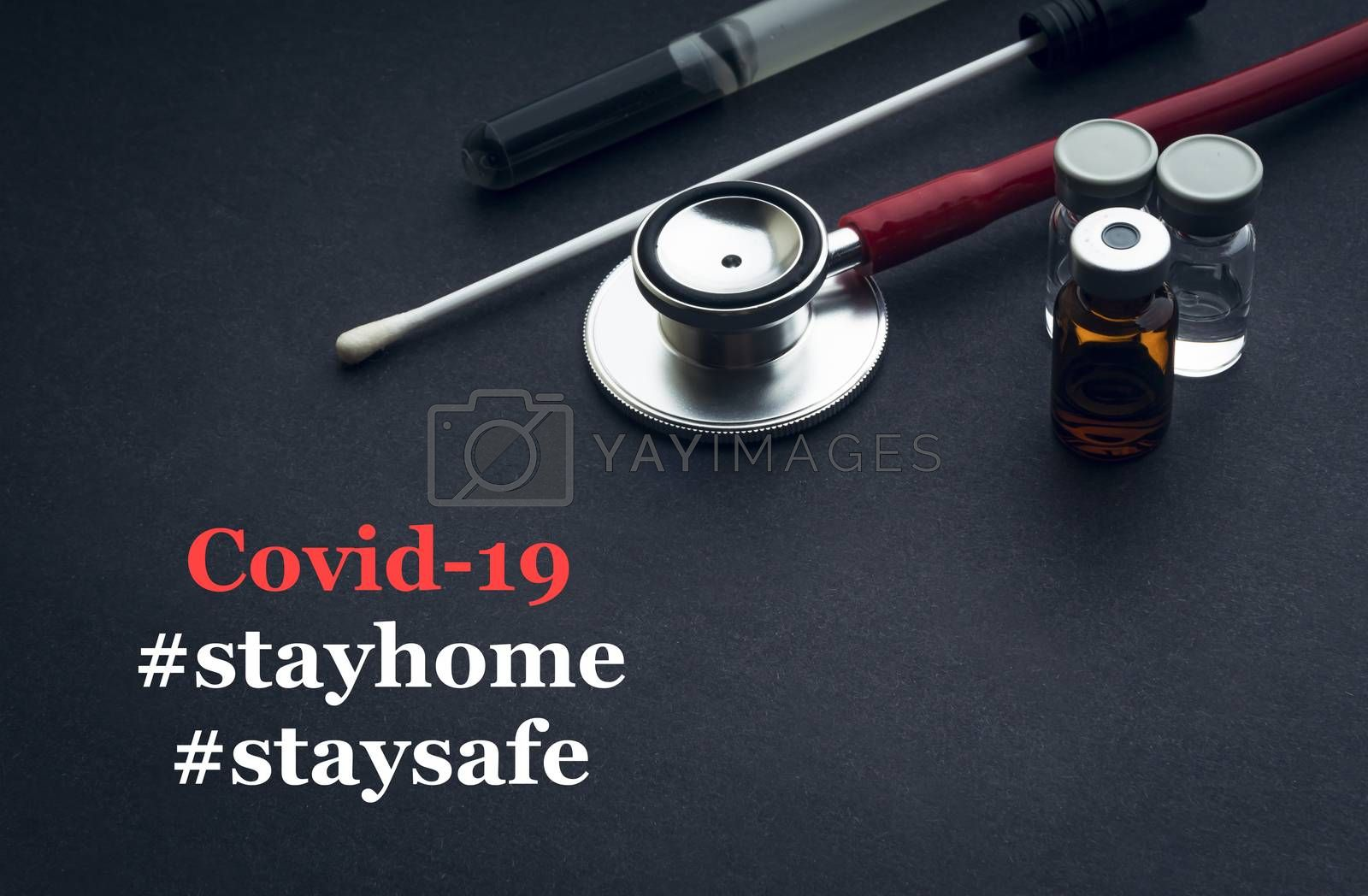 COVID-19 or CORONAVIRUS STAY HOME STAY SAFE text with stethoscope, medical swab and vial on black background. Covid-19 or Coronavirus concept.