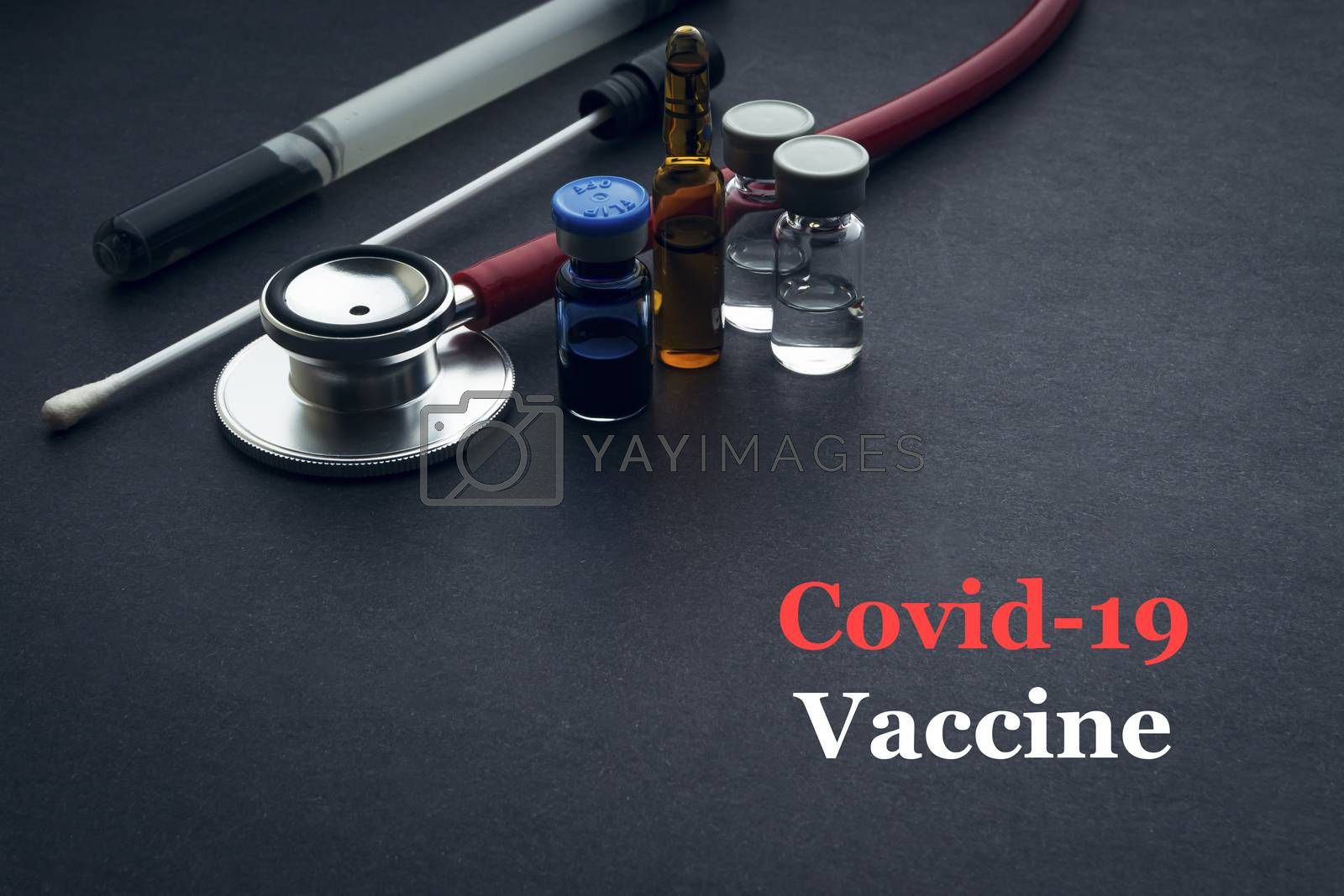 COVID-19 or CORONAVIRUS VACCINE text with stethoscope, medical swab and vial on black background. Covid-19 or Coronavirus concept.