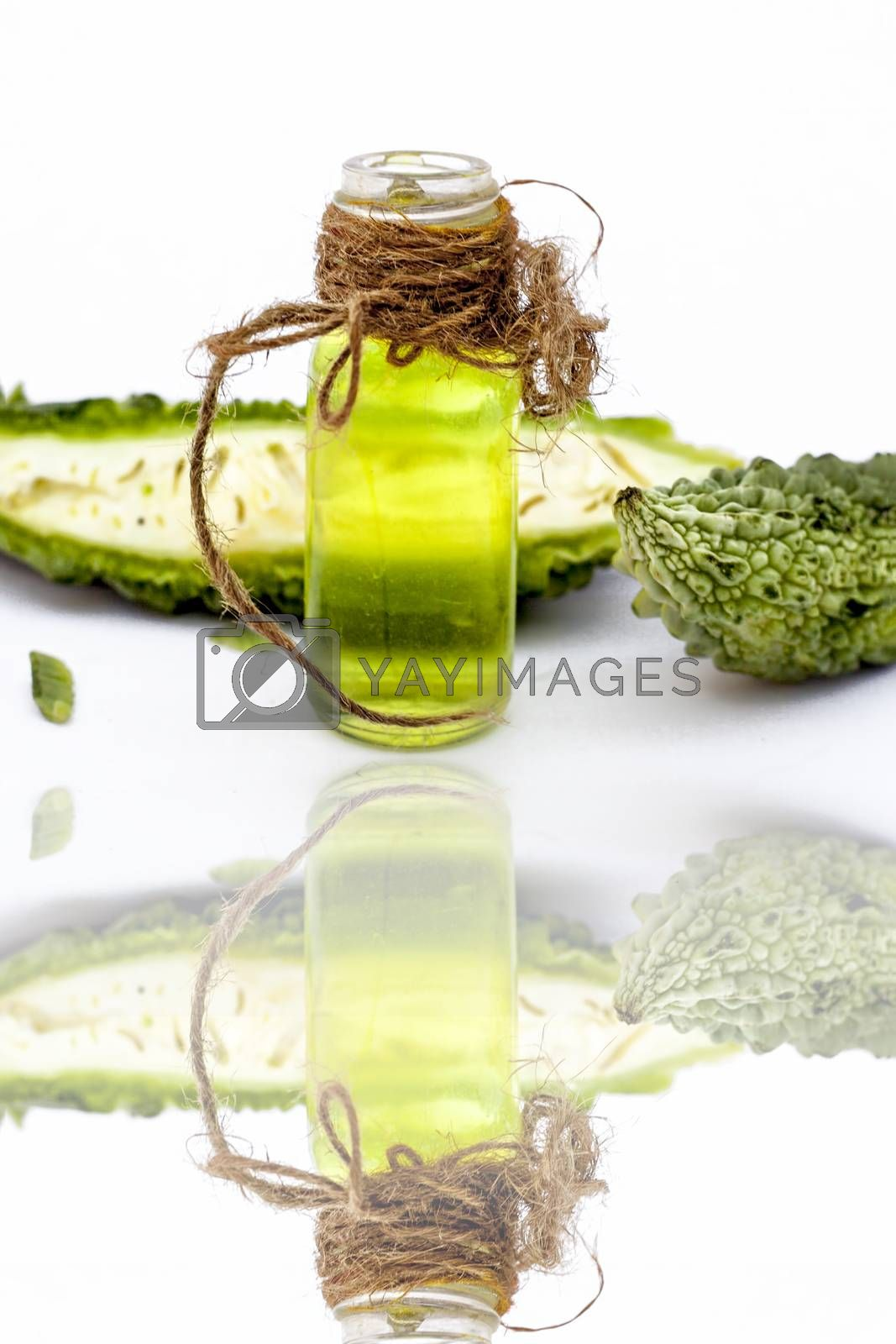 Raw organic bitter melon or Bitter Cucumber or Bitter Gourd isolated on white along with its detoxifying essential oil in a transparent glass bottle,with its reflection.