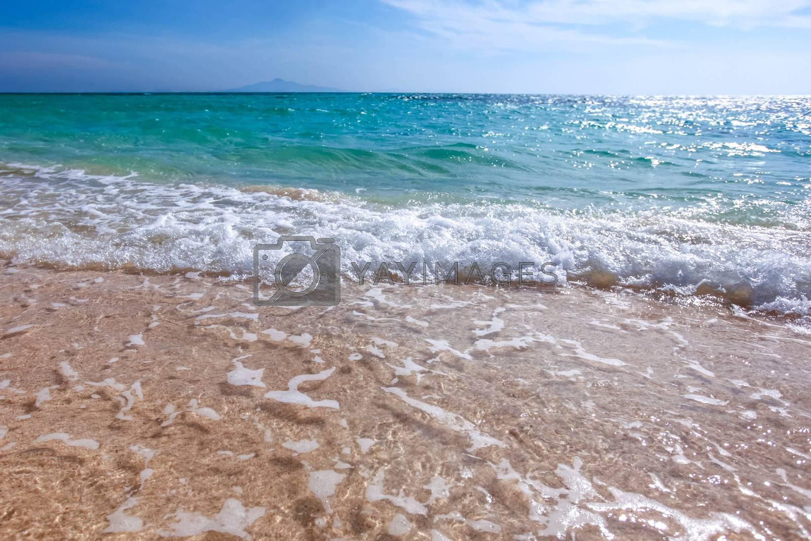 Sand beach and blue sea surf waves close up