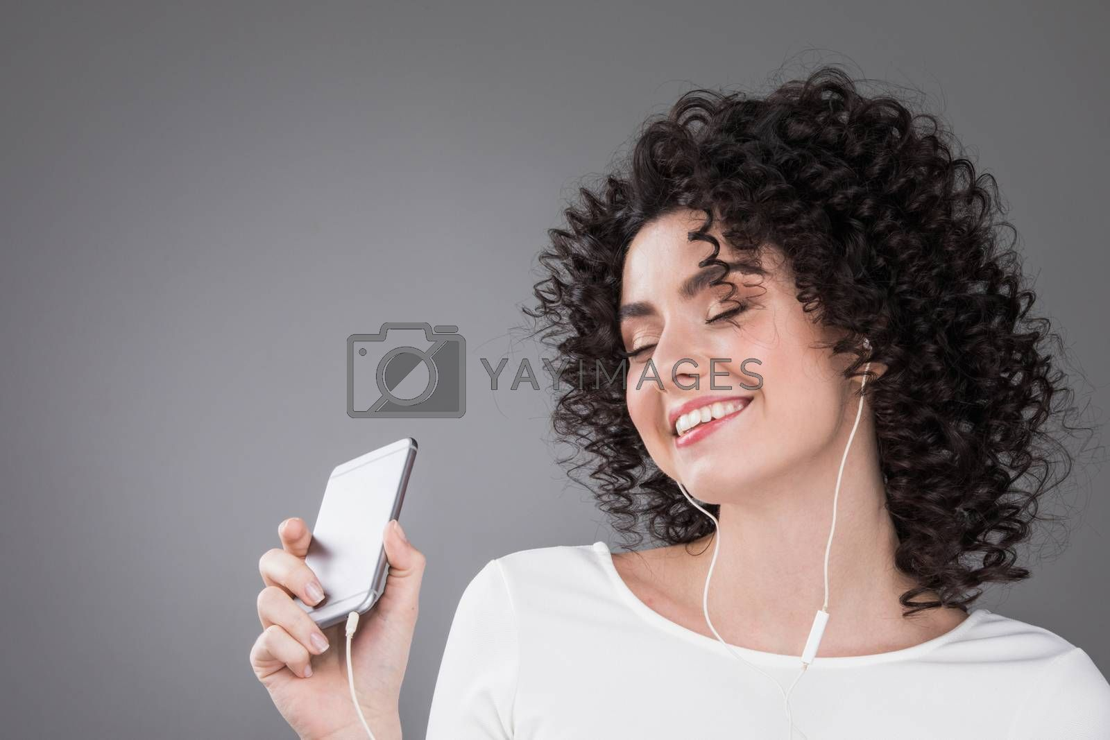 Woman in white dancing with earphones headphones listening to music on phone, gray background