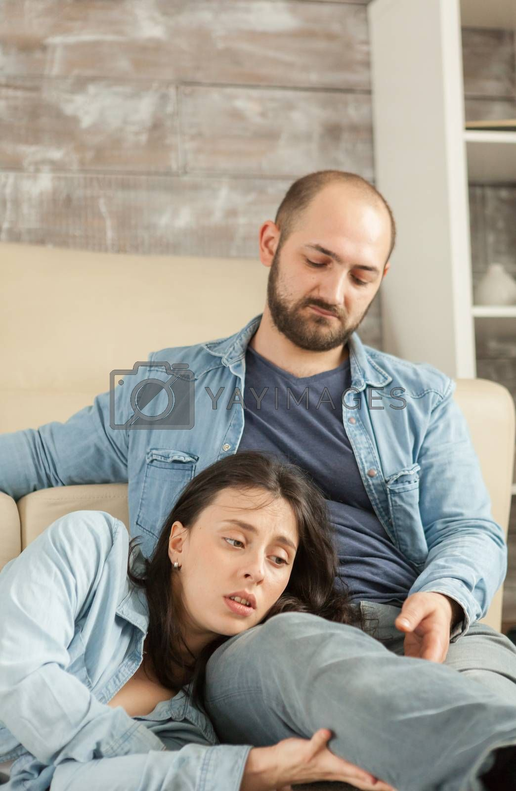 Husband looking at wife while resting together on living room rug.