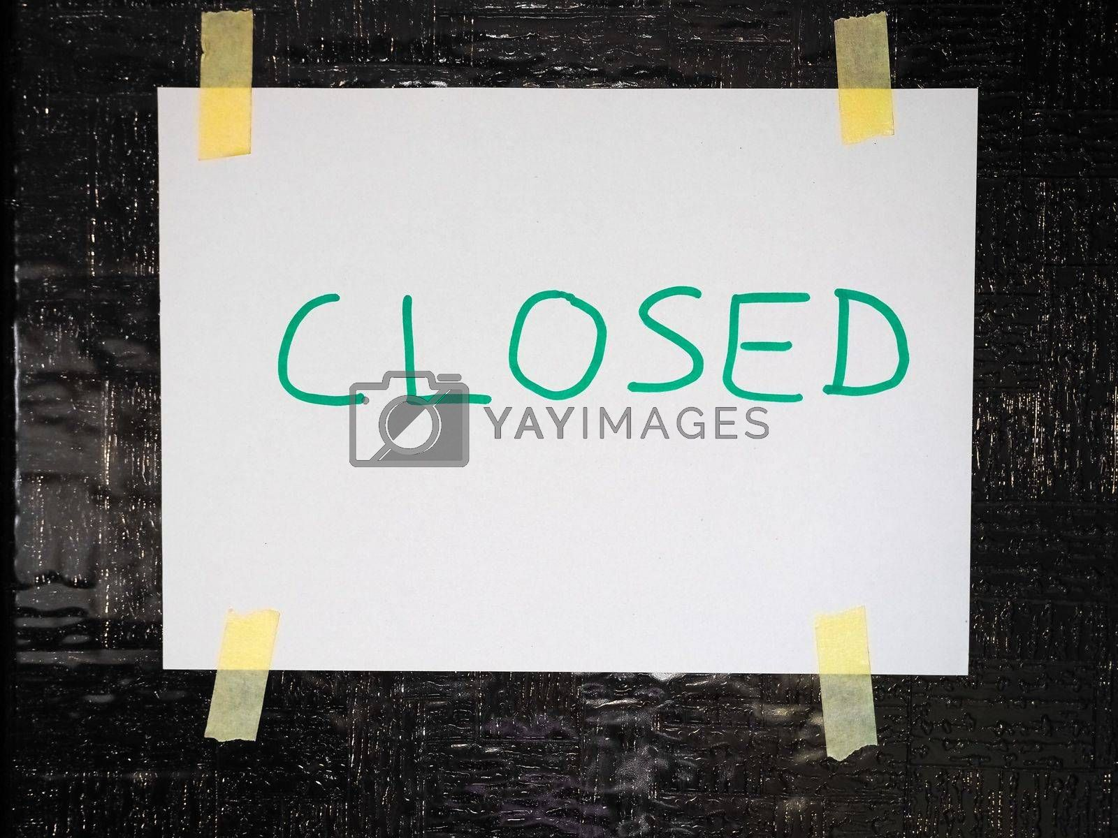 Handwritten closed sign on a shop window with reflections