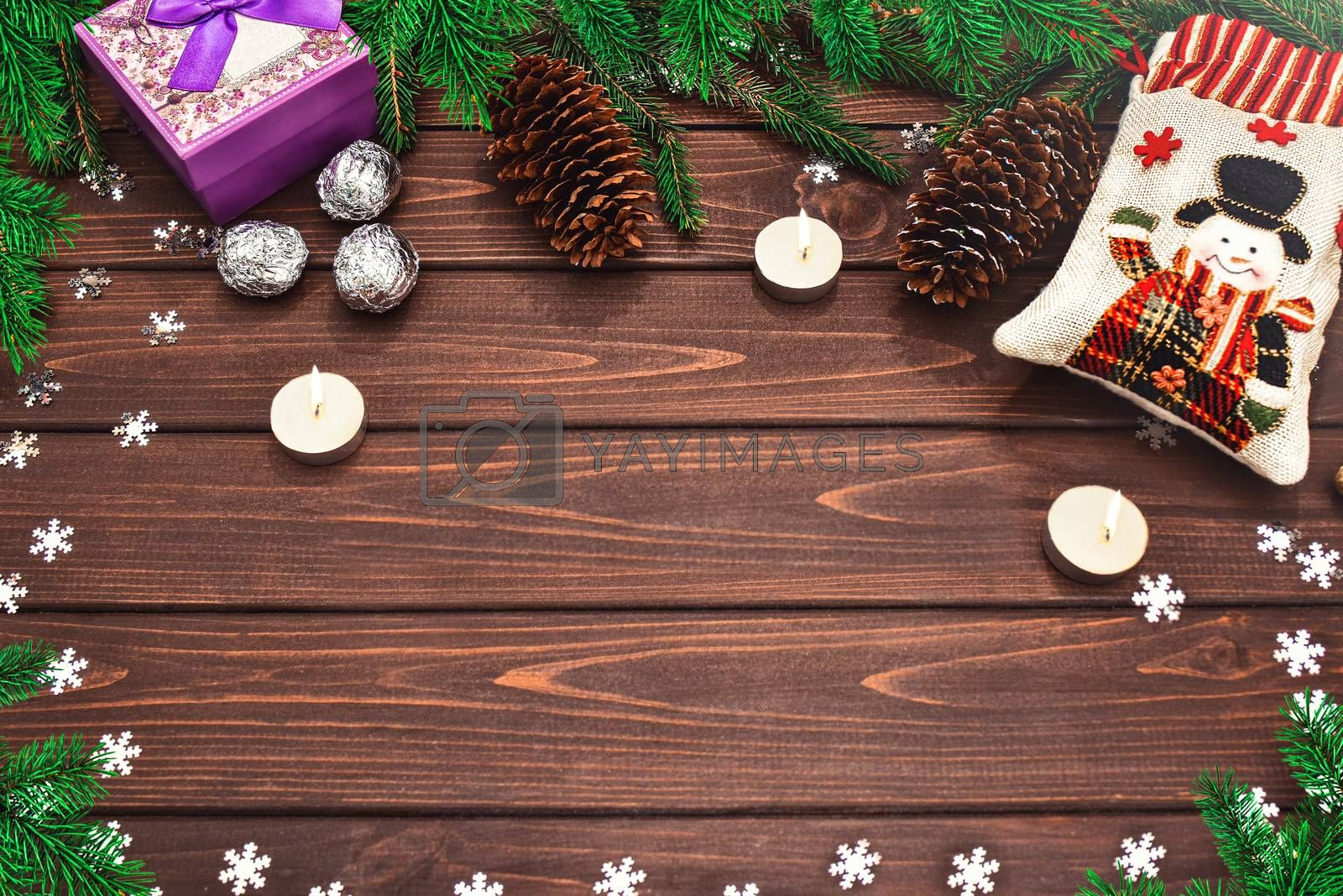 Christmas background Fir branches, cones, Candles, candy and gifts on a wooden background . Space for text. View from above. Christmas atmosphere