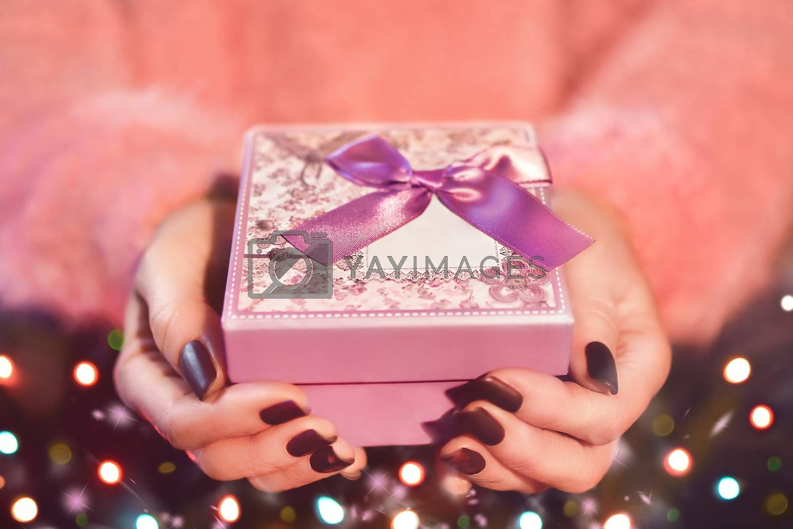 Female hand holding a pink gift box. The Valentines day and Christmas theme