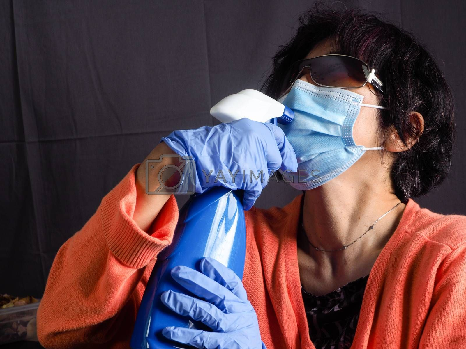 funny humorous adult asian 40s 50s woman wearing protection surgical face mask , blue latex gloves, and sun glasses pointing the head with blue sanitizer cleaning  bottle as a weapon as tired of confinement covid concept.