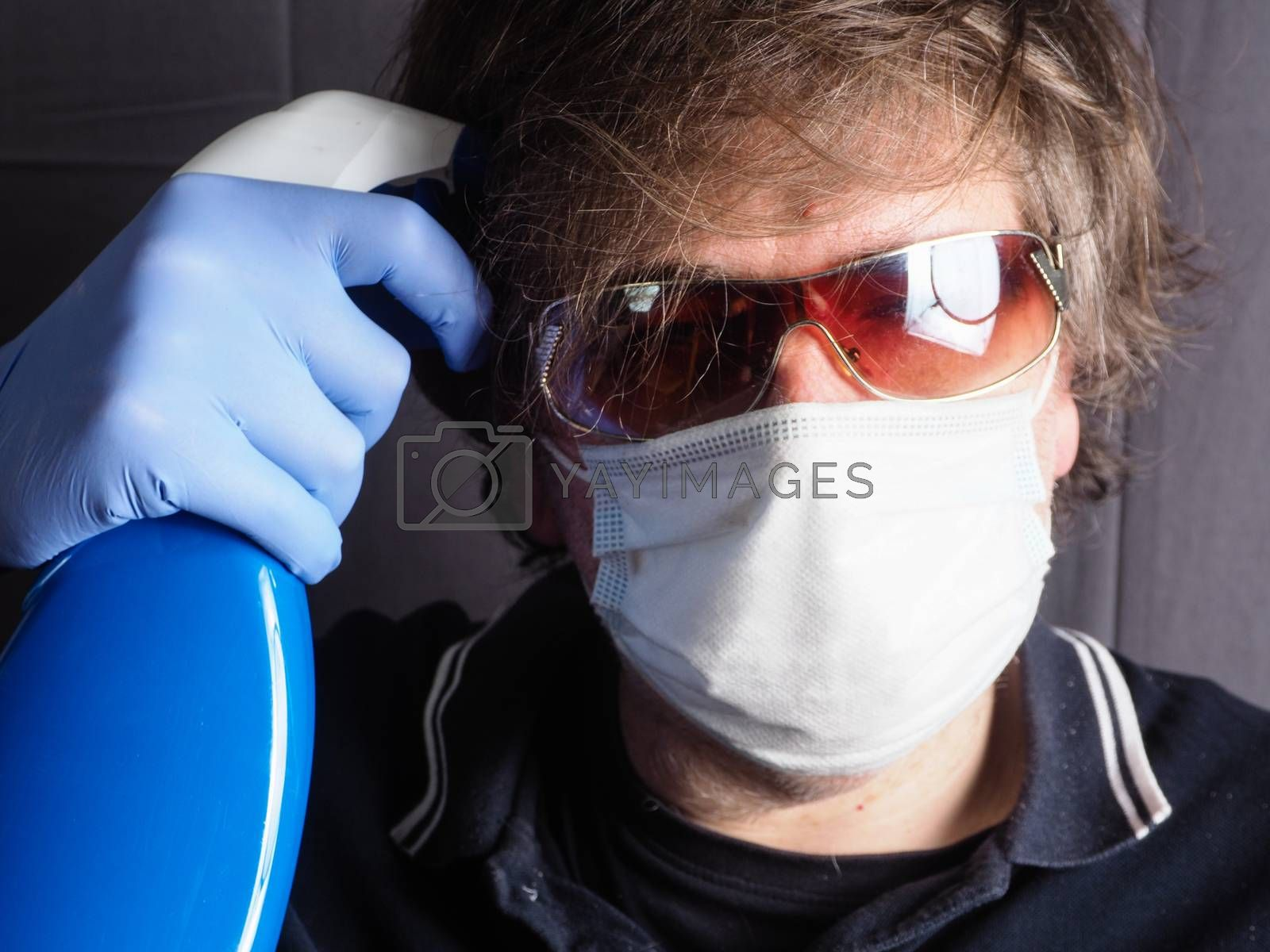 funny humorous adult caucasian 40s man wearing protection surgical face mask , blue latex gloves, and sun glasses pointing the head with blue sanitizer cleaning  bottle as a weapon as tired of confinement covid concept.