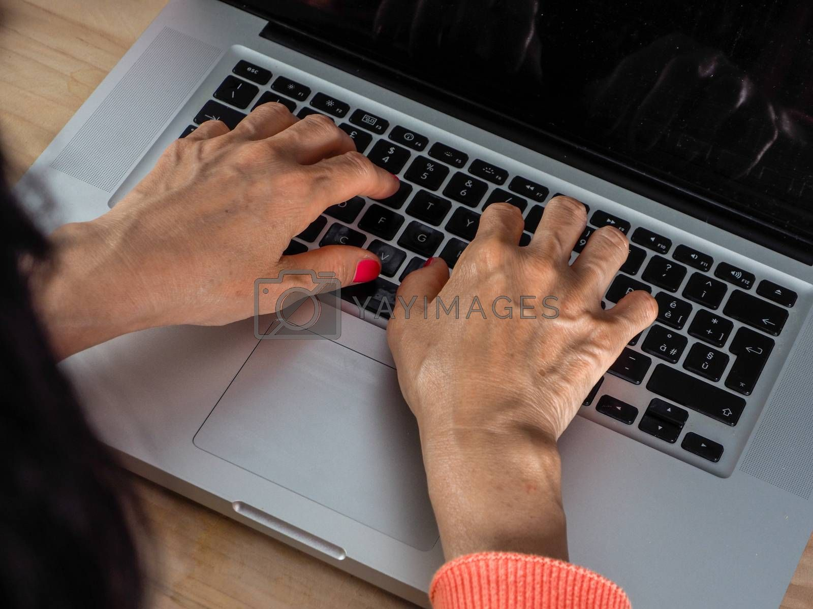 Woman hand s freelance working on a notebook laptop computer at home or home office with gel and face mask prevention items near connected to internet via hot spot of smartphone in fall, orange sweater and brown table, earth tones.