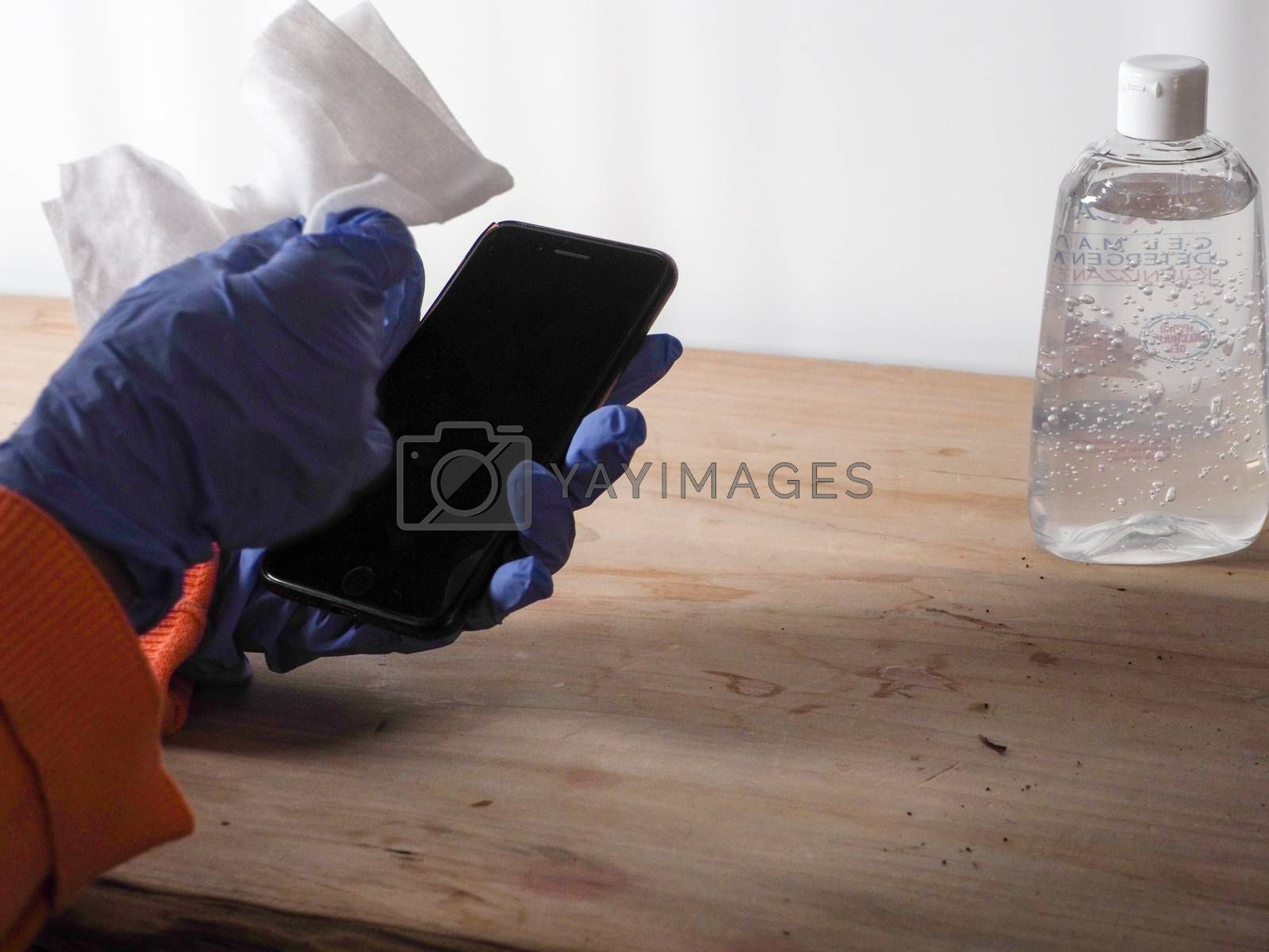close up of  woman hands wearing blue gloves while cleaning and sanitizing  smartphone  with anti virus bacterial gel against covid-19 , fall dress, orange color over a wood table, earth tones, white background and a gel bottle.
