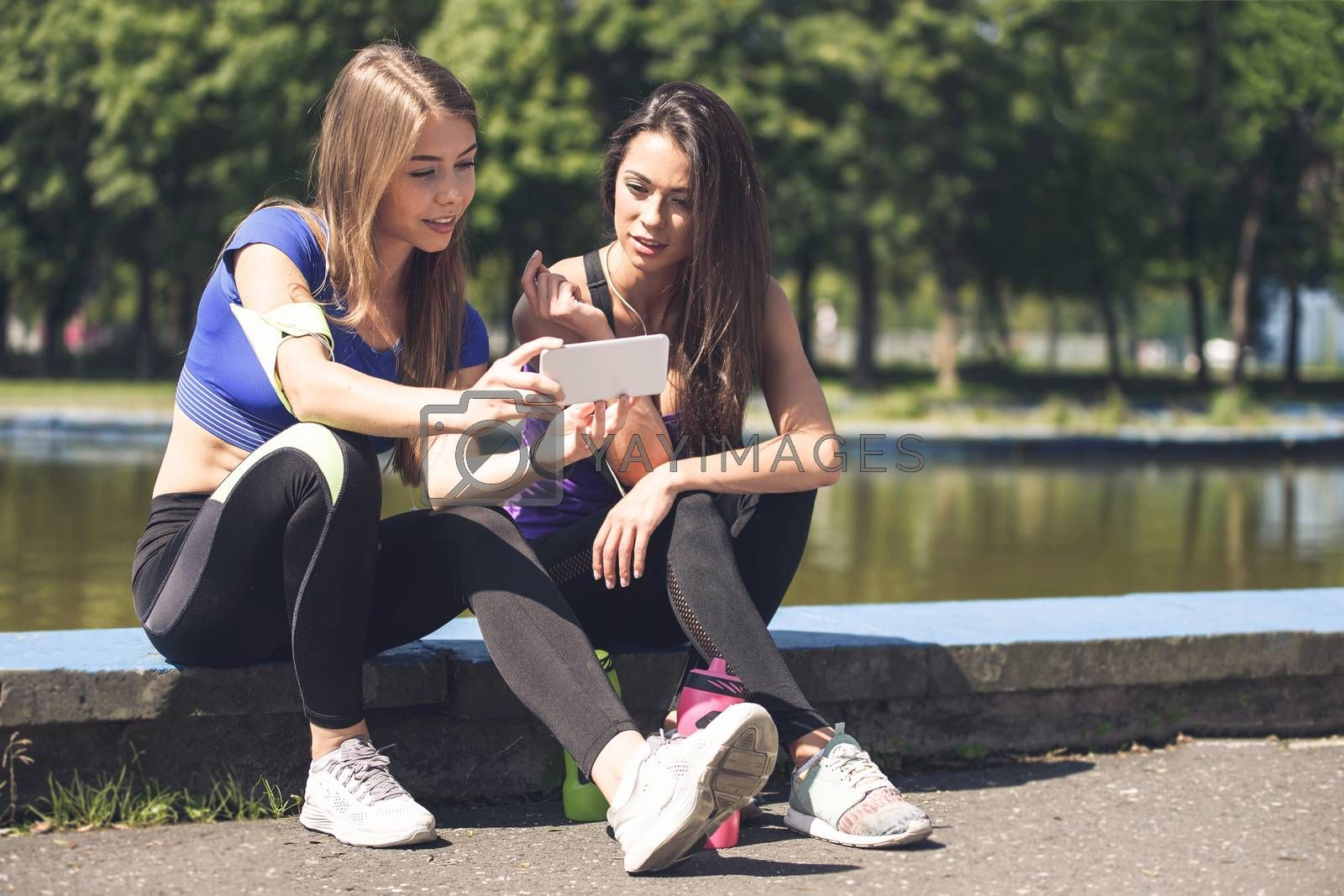 Young attractive fitness girls talking about their workout and checking sport application details on the smartphone (vintage effect)