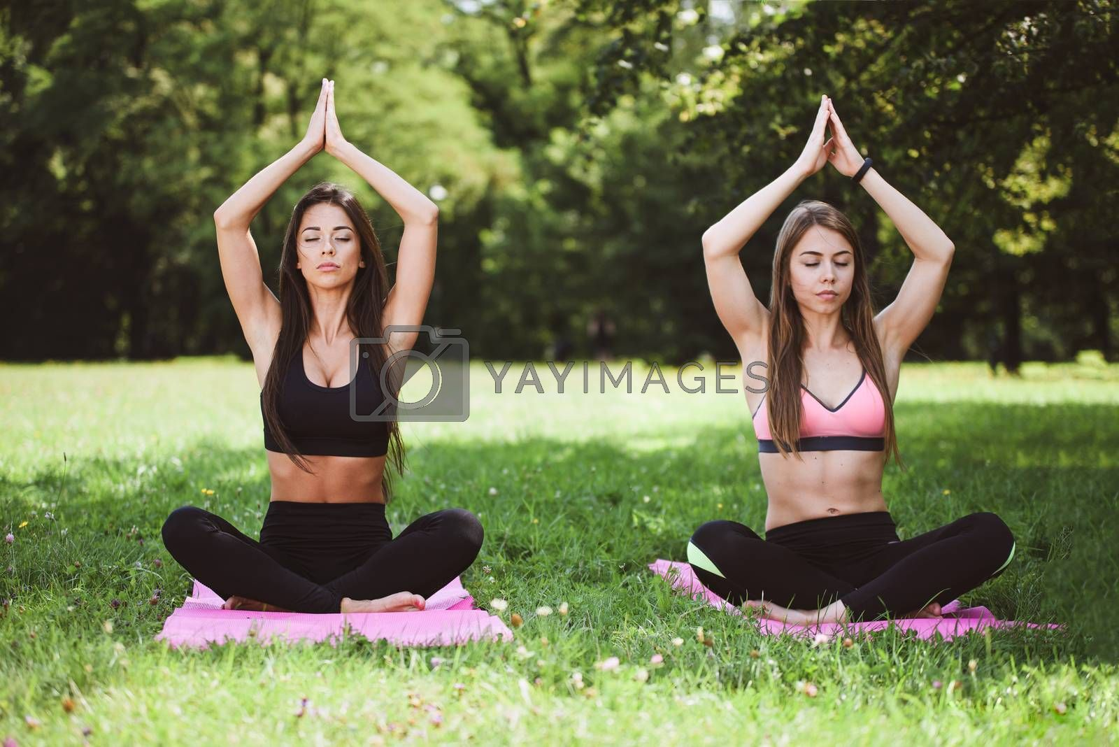 Two women doing yoga meditation in a lotus pose outdoors in a park on a sunny day (vintage effect)
