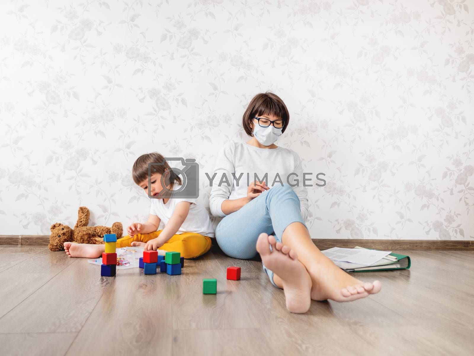 Mom and son at home quarantine because of coronavirus COVID19. Mother works remotely with laptop, son plays with toy blocks. Self isolation at home.