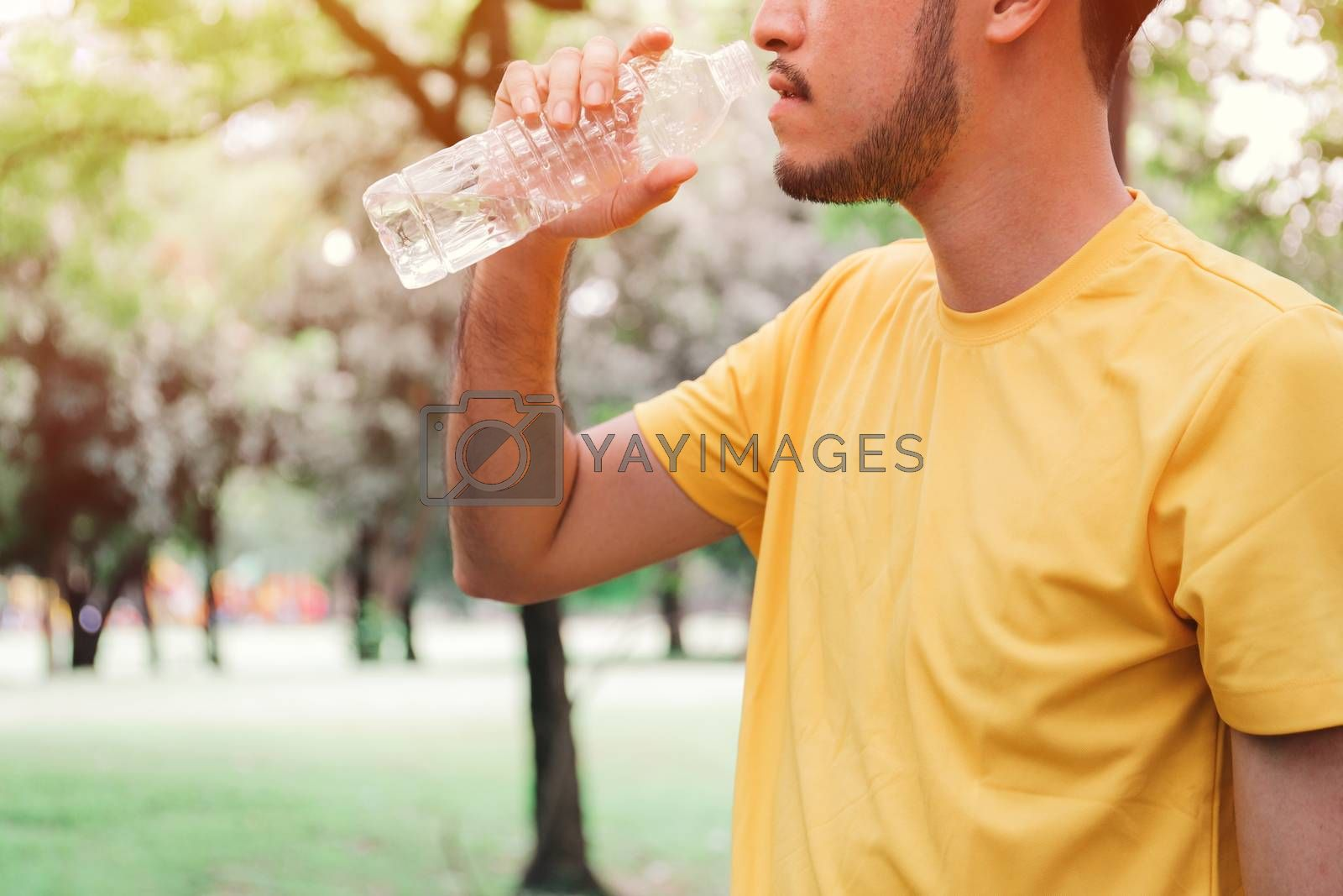 Young asian man jogger drinking water from the bottle after hard exercise in the garden, healthy concept