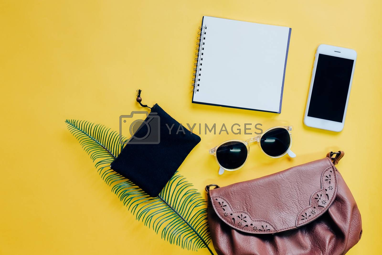 Top view flat lay of woman bag with smartphone, blank notebook, sunglasses and green leaf on yellow background, copy space