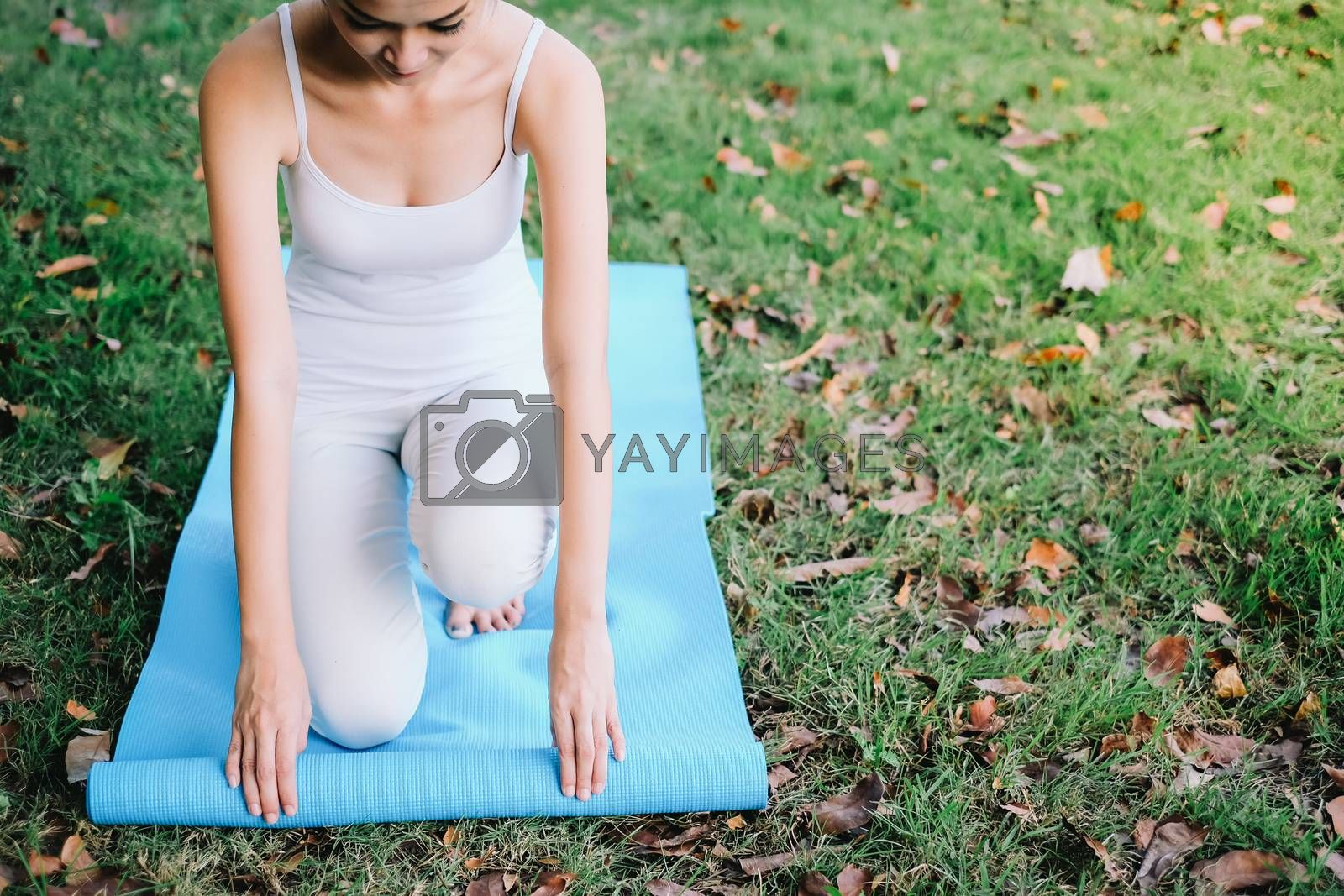 Attractive young asian woman rolling up fitness mat on green grass in the park, preparing for working out in the morning