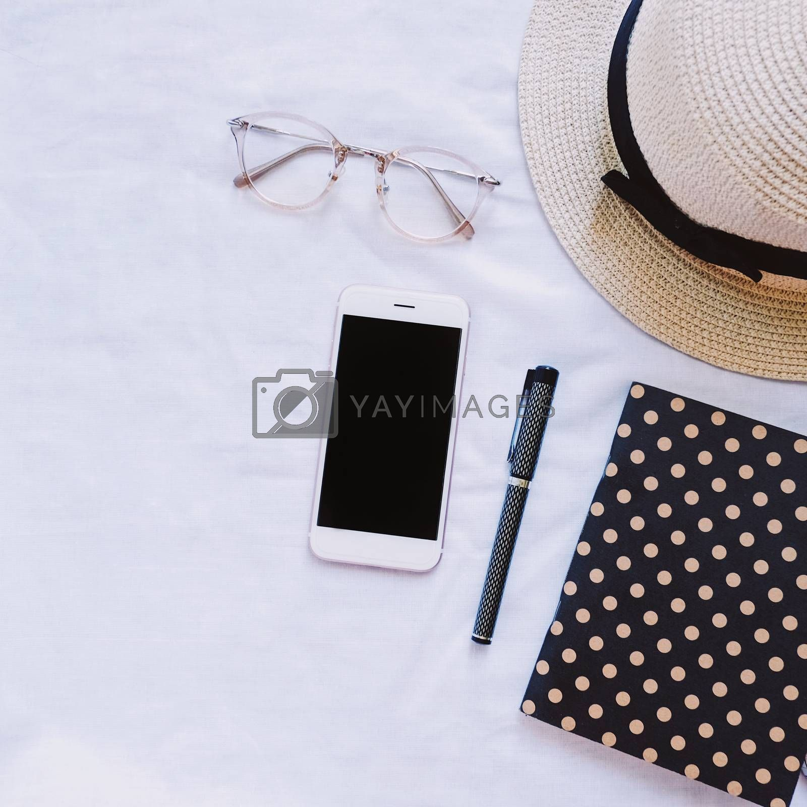 Top view of accessories, hat, eyeglasses, notebook and smartphone on white background, lifestyle concept