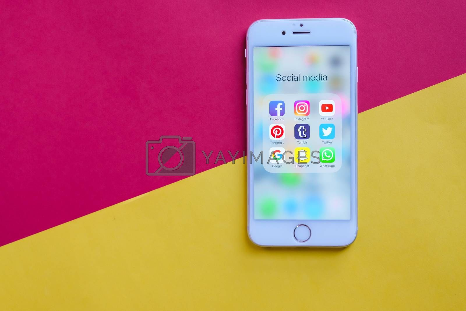 BANGKOK, THAILAND - NOVEMBER 28, 2016: Apple iPhone 6s screen showing group of popular social networks icons on yellow and red background, Social media are most popular tool for communication.
