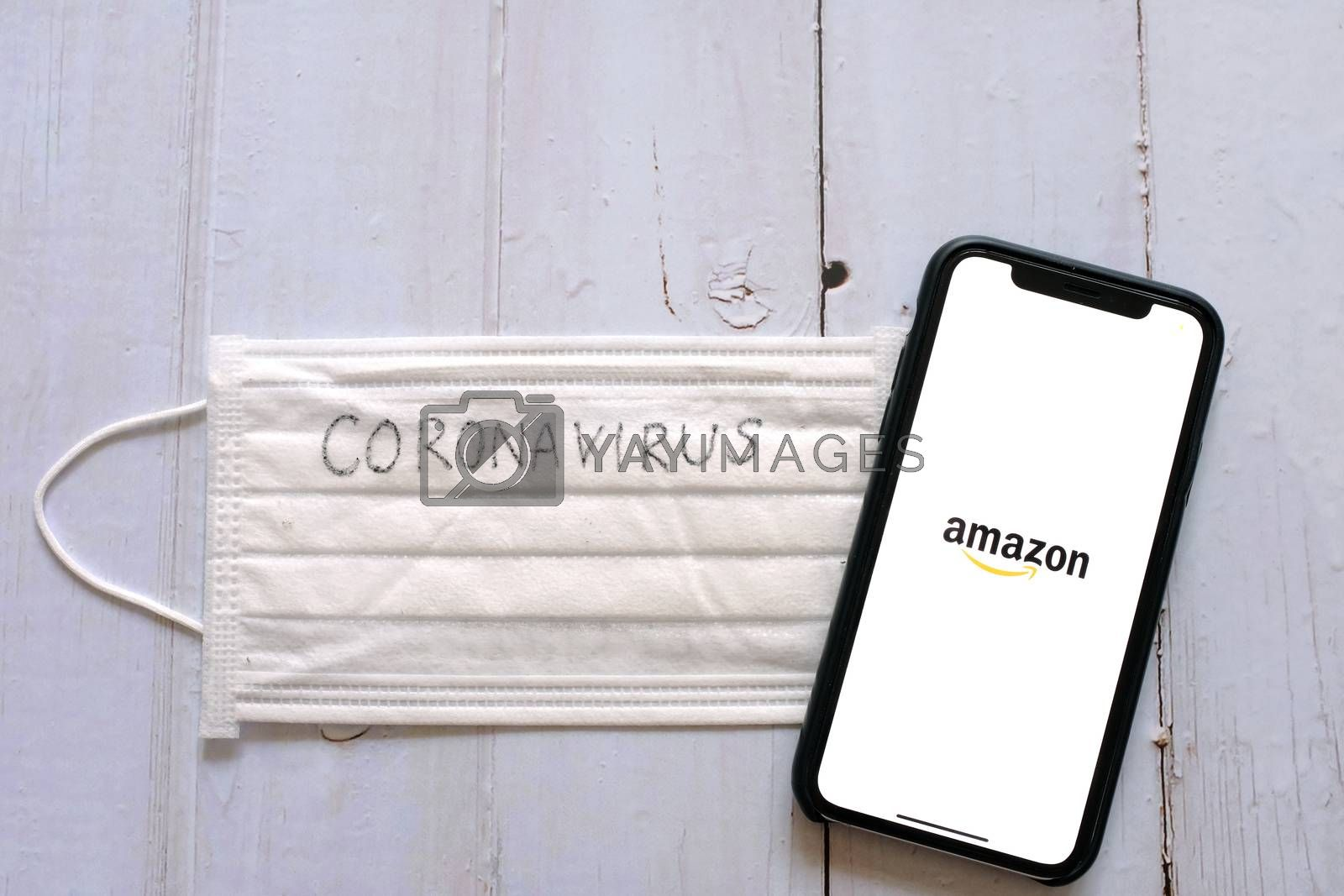 BANGKOK, Thailand - April 2, 2020 : Flat lay of iPhone showing amazon application and mask written with coronavirus. Amazon is popular shopping online retailer during COVID-19 and Coronavirus