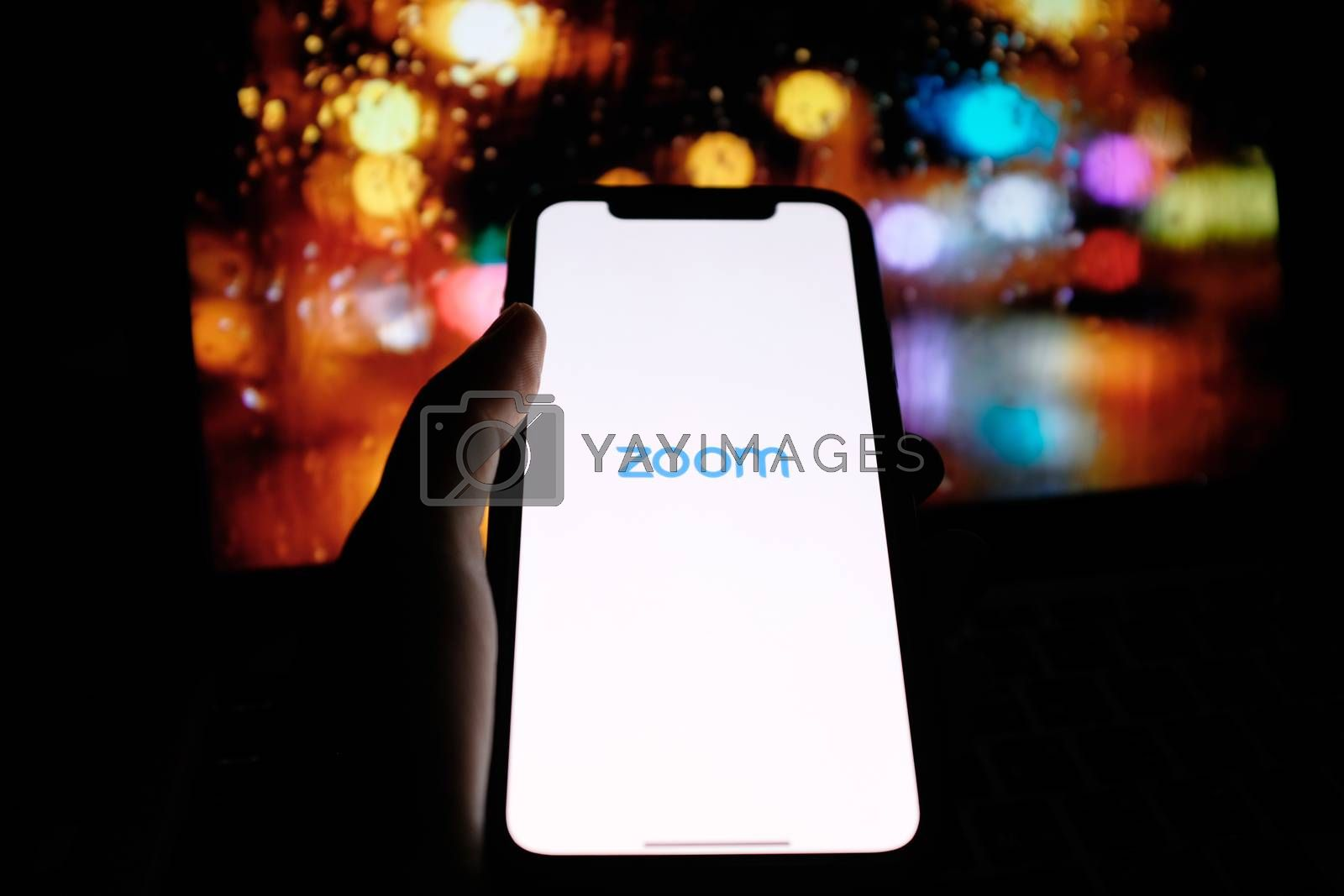 BANGKOK, Thailand - April 6, 2020 : Hand holding iPhone showing zoom application with night bokeh background at night. Zoom is popular cloud meeting or video conference during COVID-19 and Coronavirus