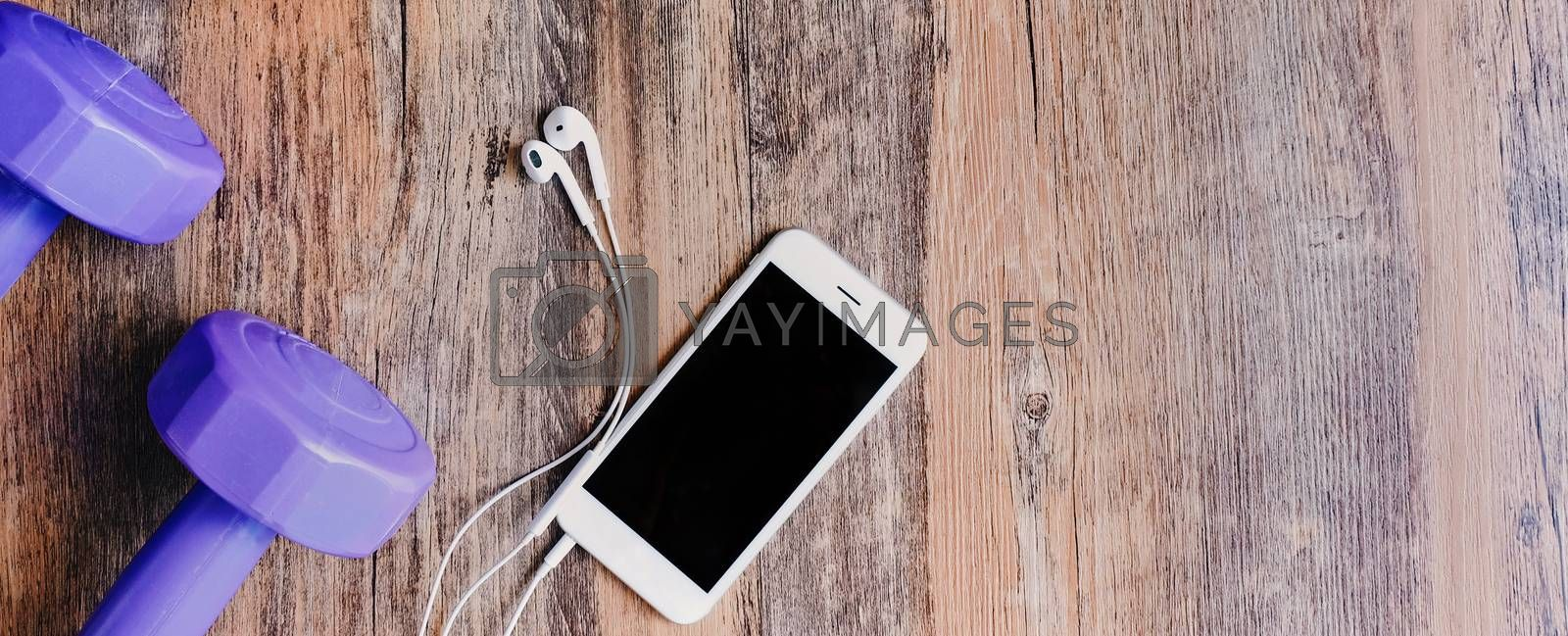 Top view of flat lay fitness items with smartphone, earphones and dumbbell on wooden background, photo banner for website header design with copy space for text