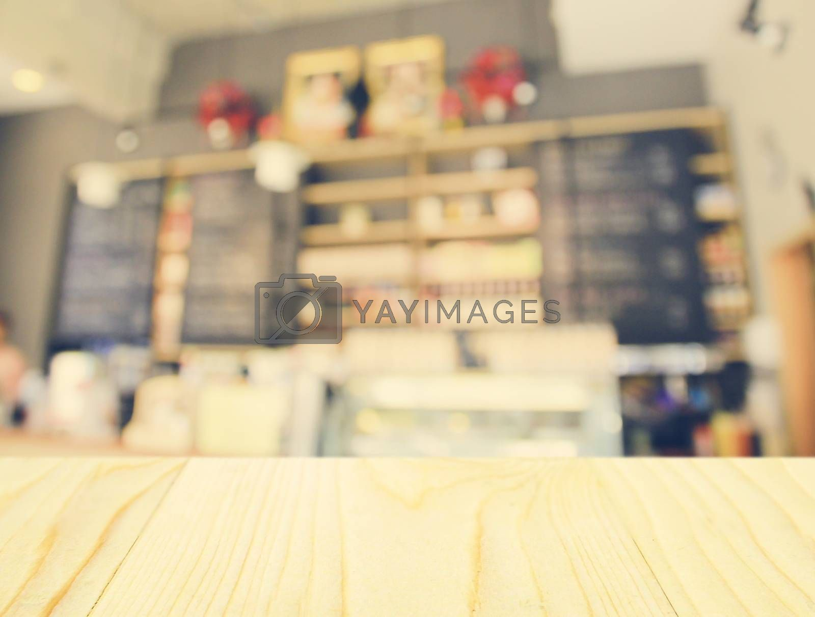 Royalty free image of Empty wooden table and blurred cafe background by nuchylee