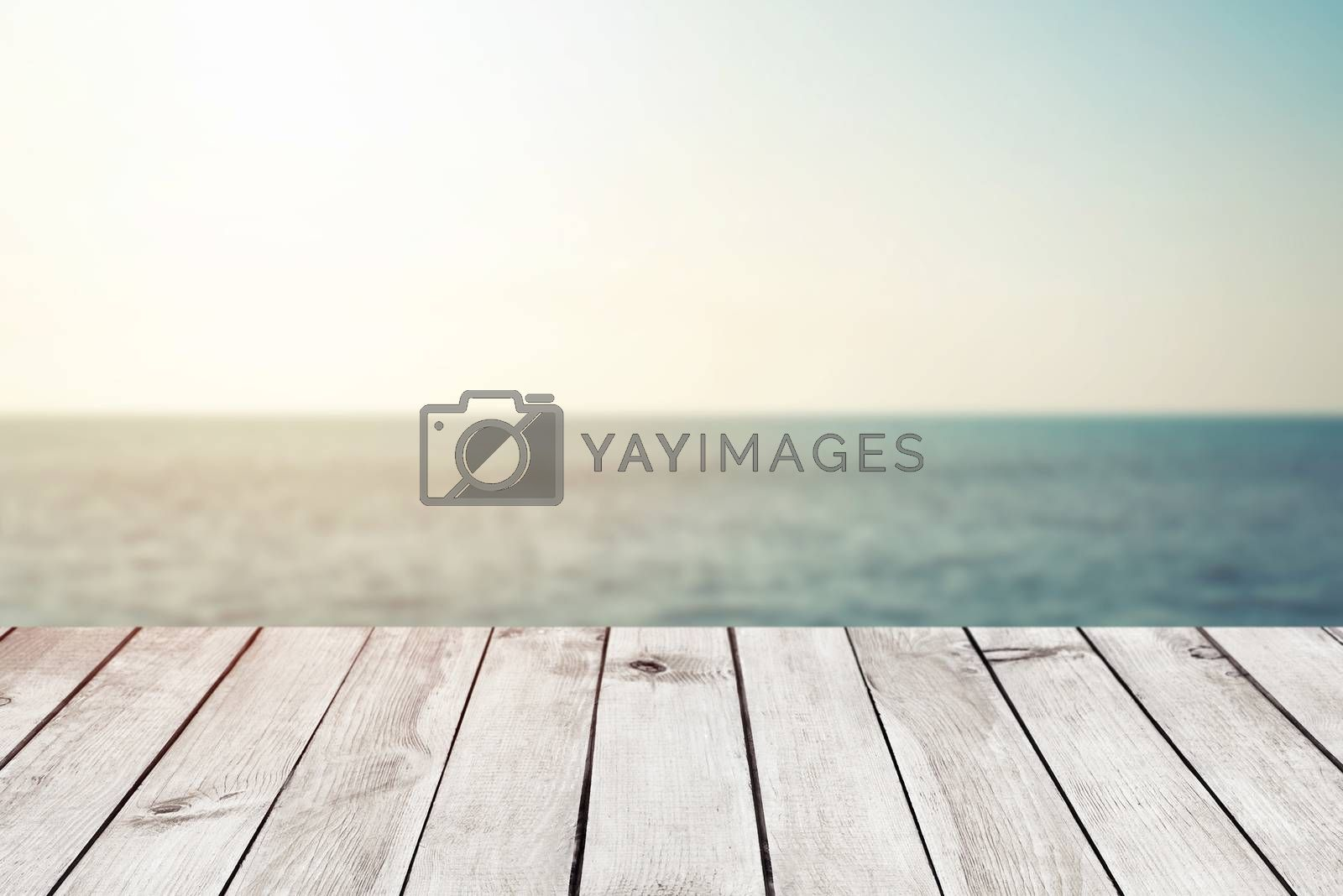 Empty wood table top on blur abstract sea beach background with sunlight, for montage product display