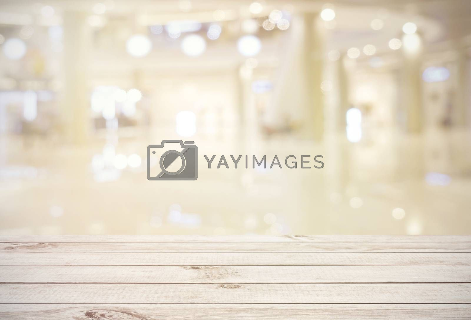 Royalty free image of Empty wooden board table top on blur abstract of shopping mall b by nuchylee