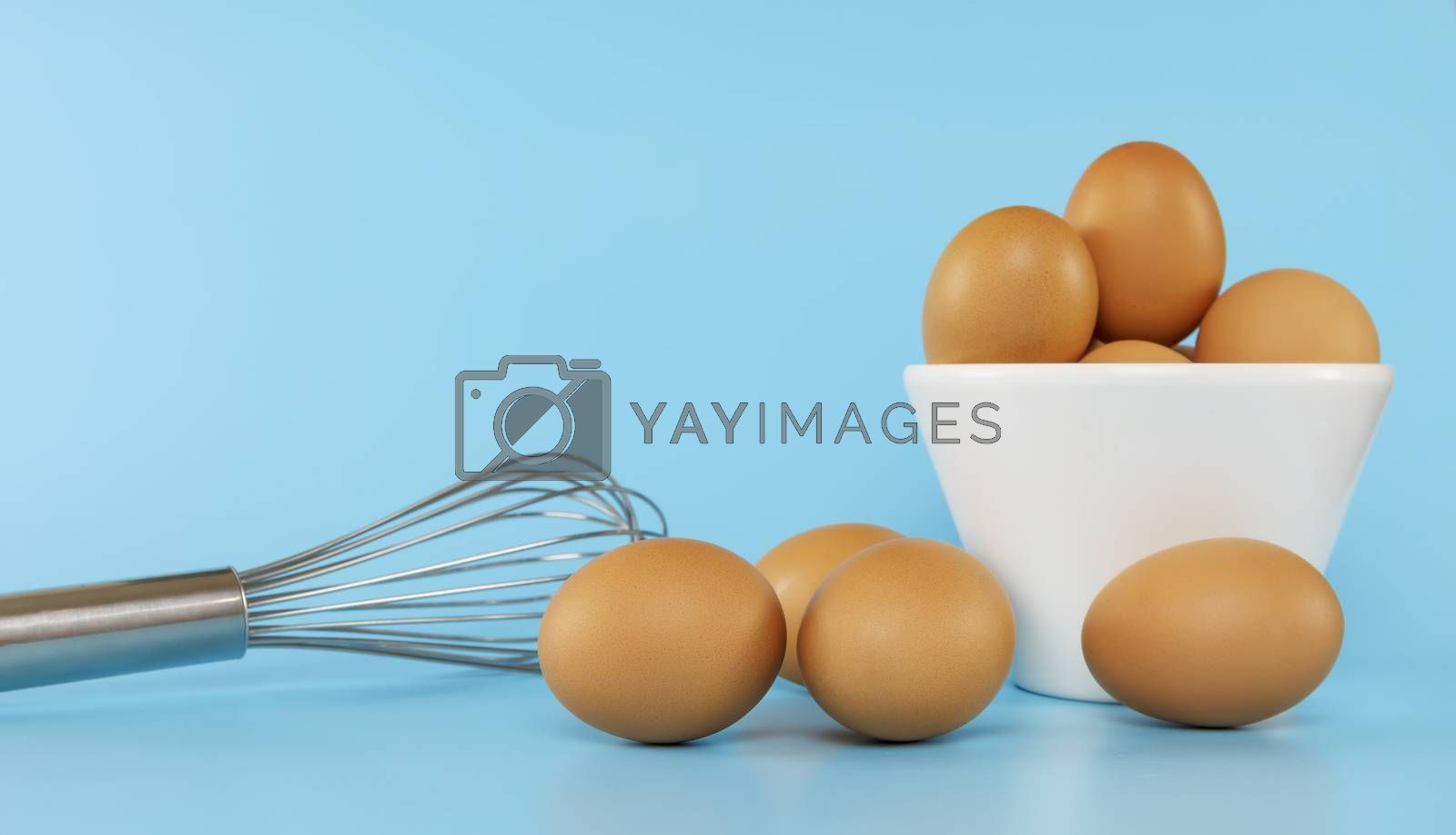 Fresh chicken eggs in white bowl and chicken eggs on blue background with copy space. Uncooked raw eggs in bowl and whisk isolated .