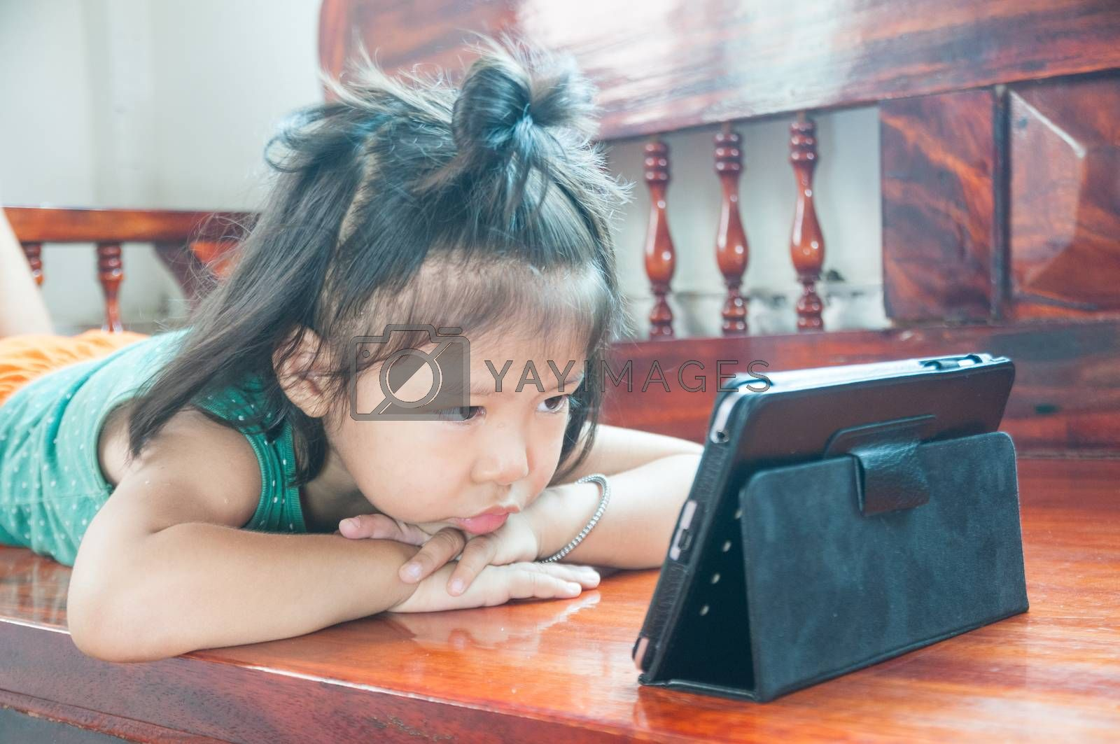 Unhappy Young Girl lying on wooden stool and Learning online course on Wireless Digital Tablet while staying at home in situation of Corona Virus or Covid 19 outbreak.