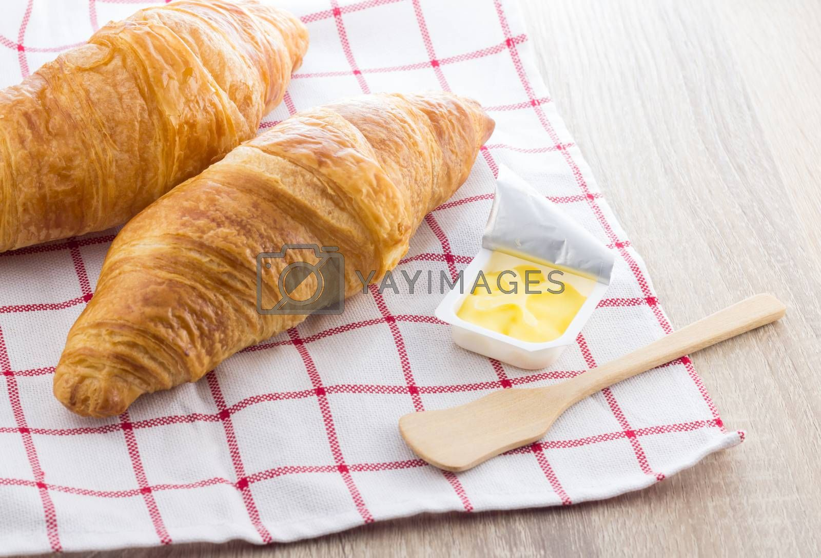 French croissant and butter on wooden background