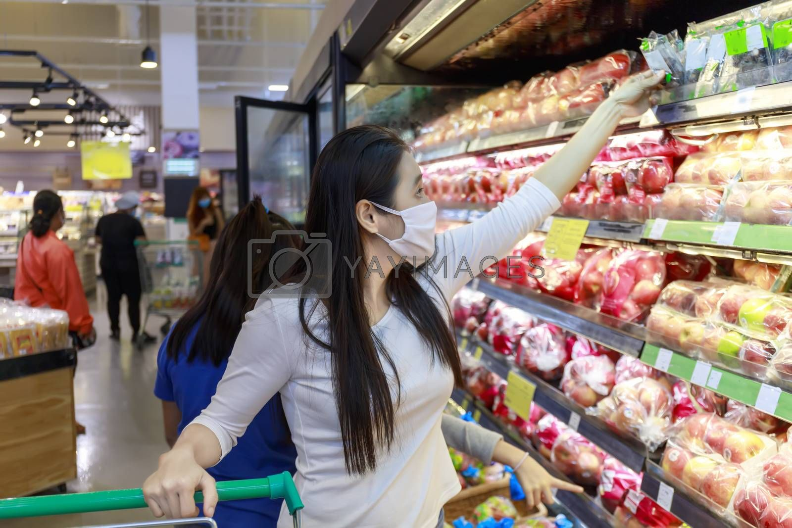 Asian woman wear face mask push shopping cart in suppermarket departmentstore. Girl, looking grocery to buy  fruit. Women wearing protective face mask hold shopping cart New normal after covid-19.