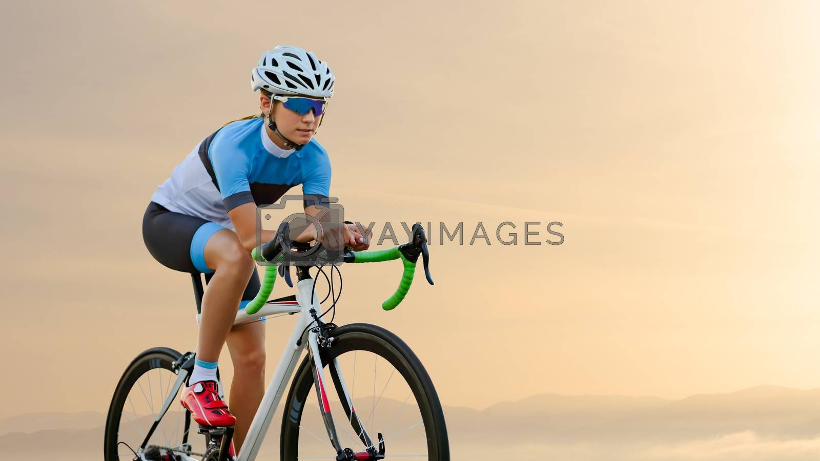 Young Woman Cyclist Riding Road Bike on the Road in the Beautiful Mountains at Sunset. Adventure, Travel, Healthy Lifestyle and Sport Concept.