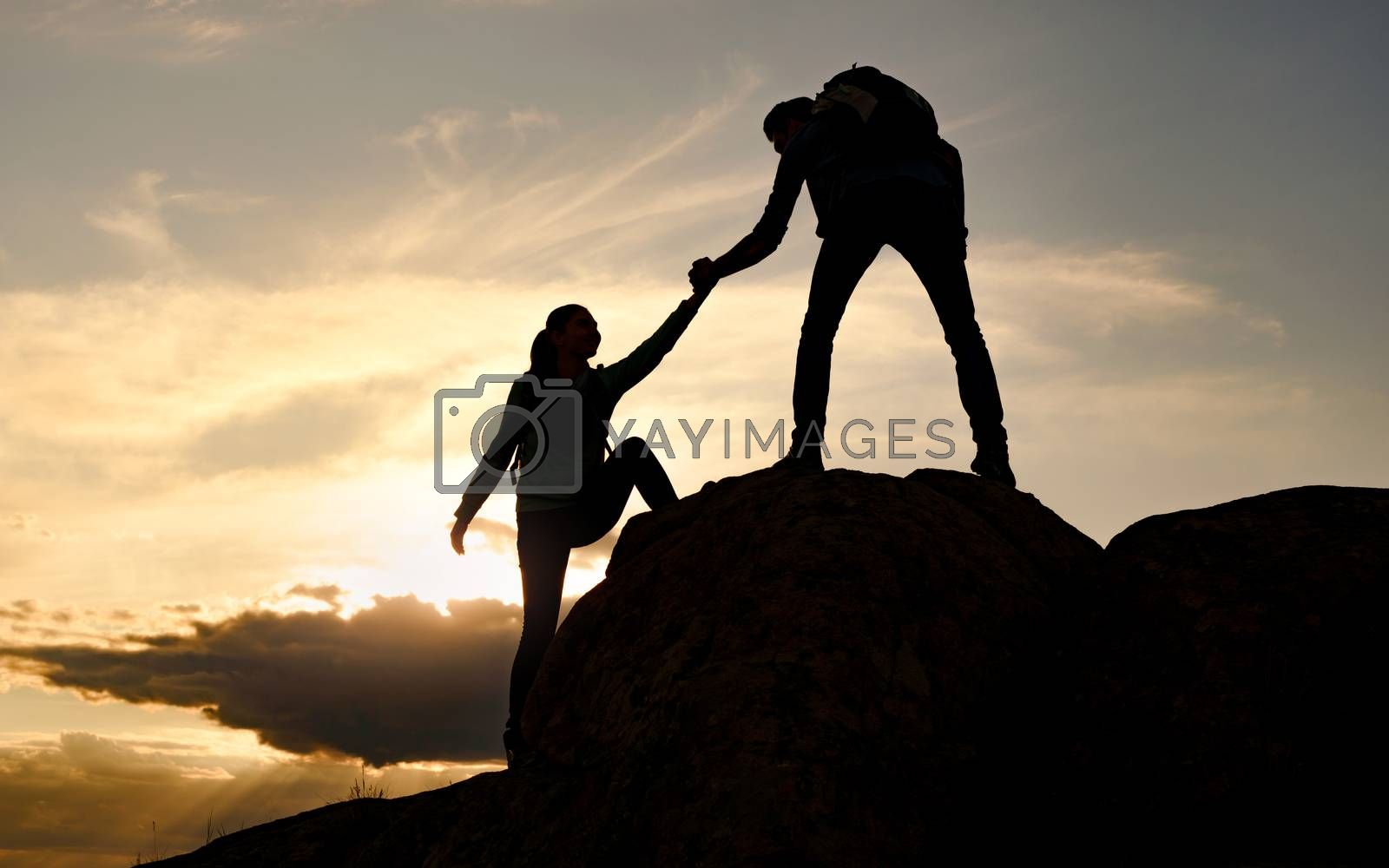 Couple of Young Happy Travelers with Backpacks Hiking in the Mountains at Warm Summer Sunset. Man Helping Woman to Climb to the Top of the Rock. Family Travel and Adventure Concept.