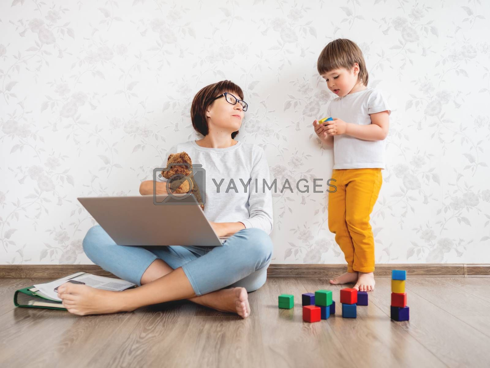 Mom and son at home. Mother works remotely with laptop, son plays near her. Freelance work in same time with raising children.