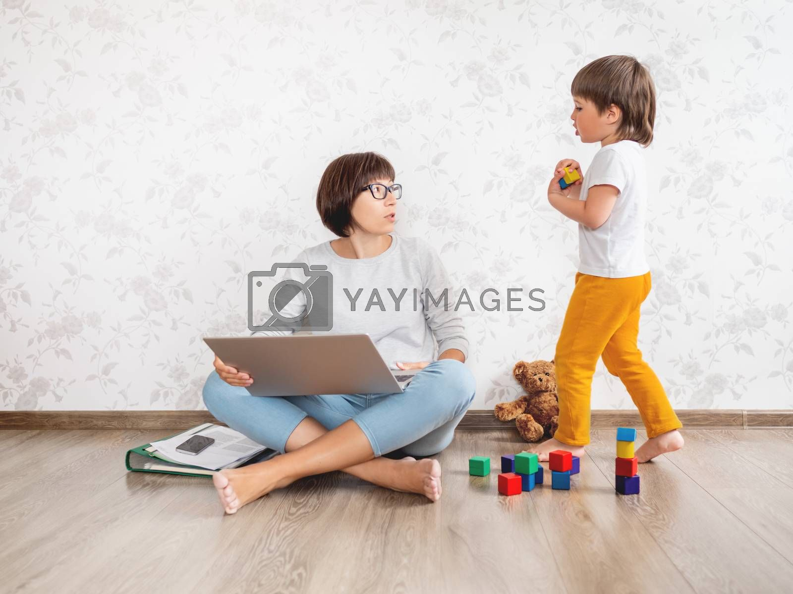Mom and son at home. Mother works remotely with laptop, kid plays near her. Freelance work in same time with raising children.