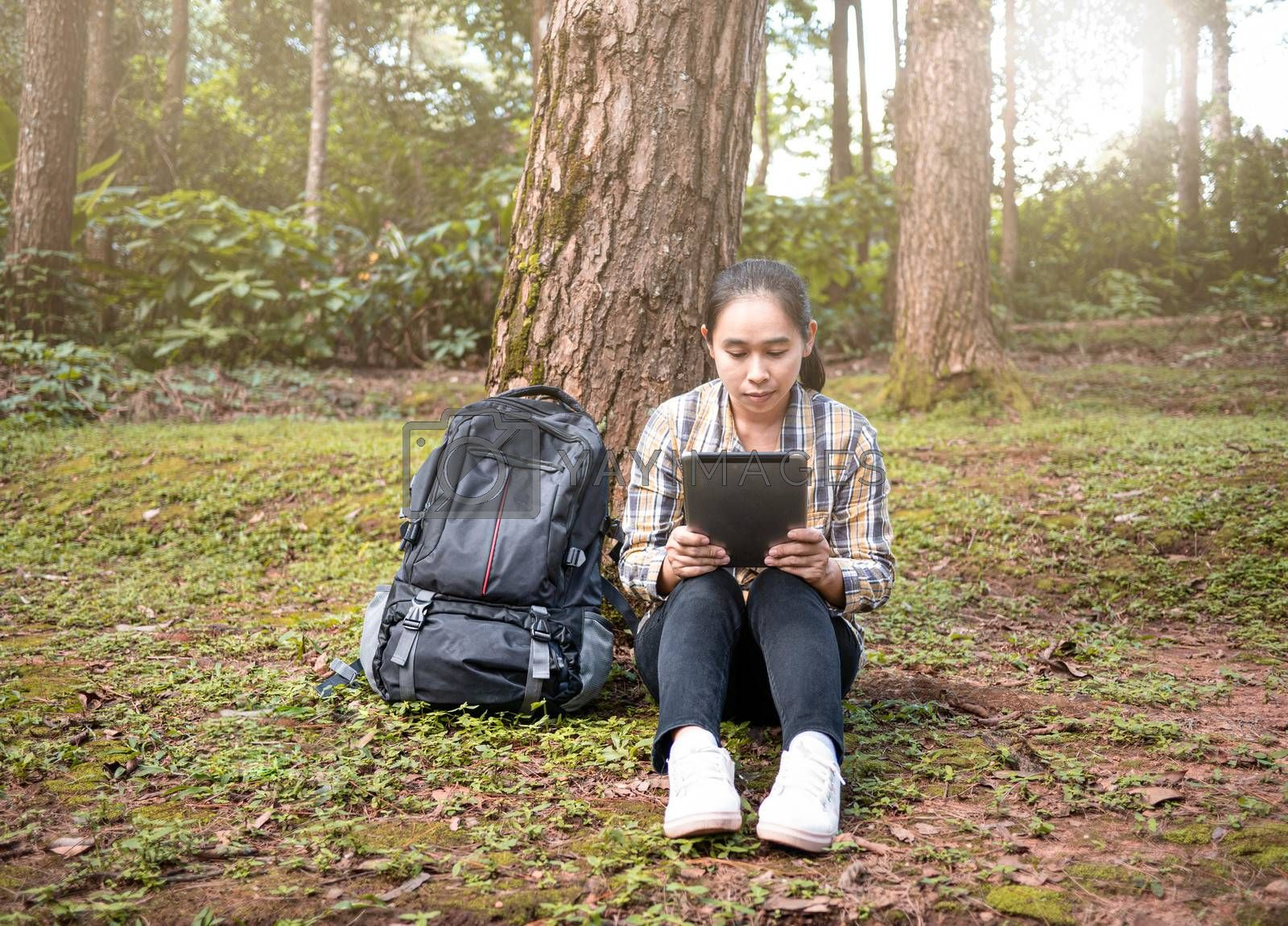 Young woman traveler searches GPS coordinates by tablet PC at nature trail in summer vacations day. Technology and Travel concept.
