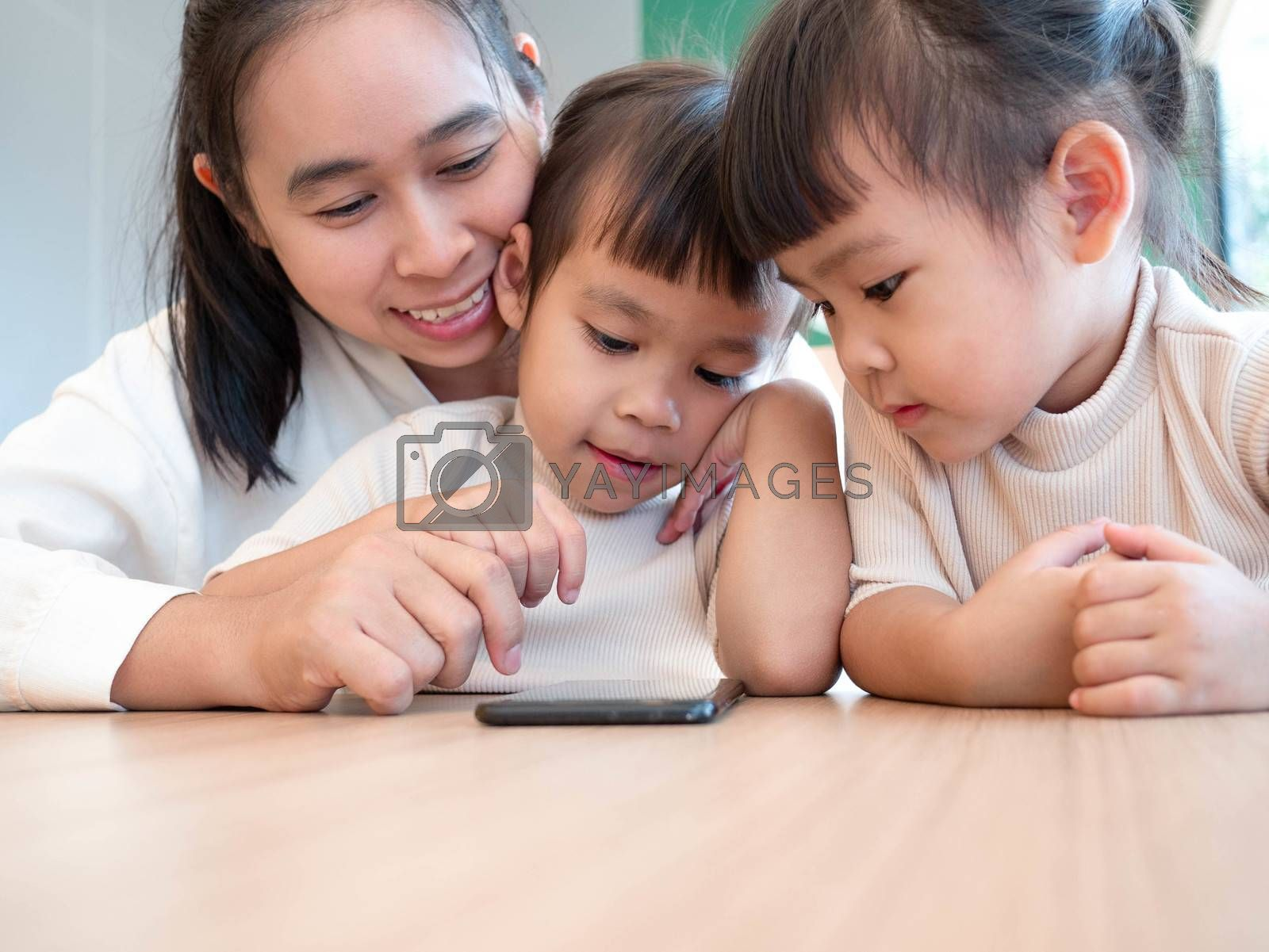 Asian beautiful young mother and her little daughters are enjoying playing games or entertaining using mobile apps on phone at home.