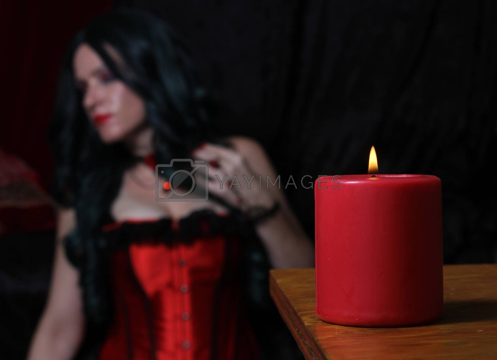 Red Candle With Woman in Red Corset in Background