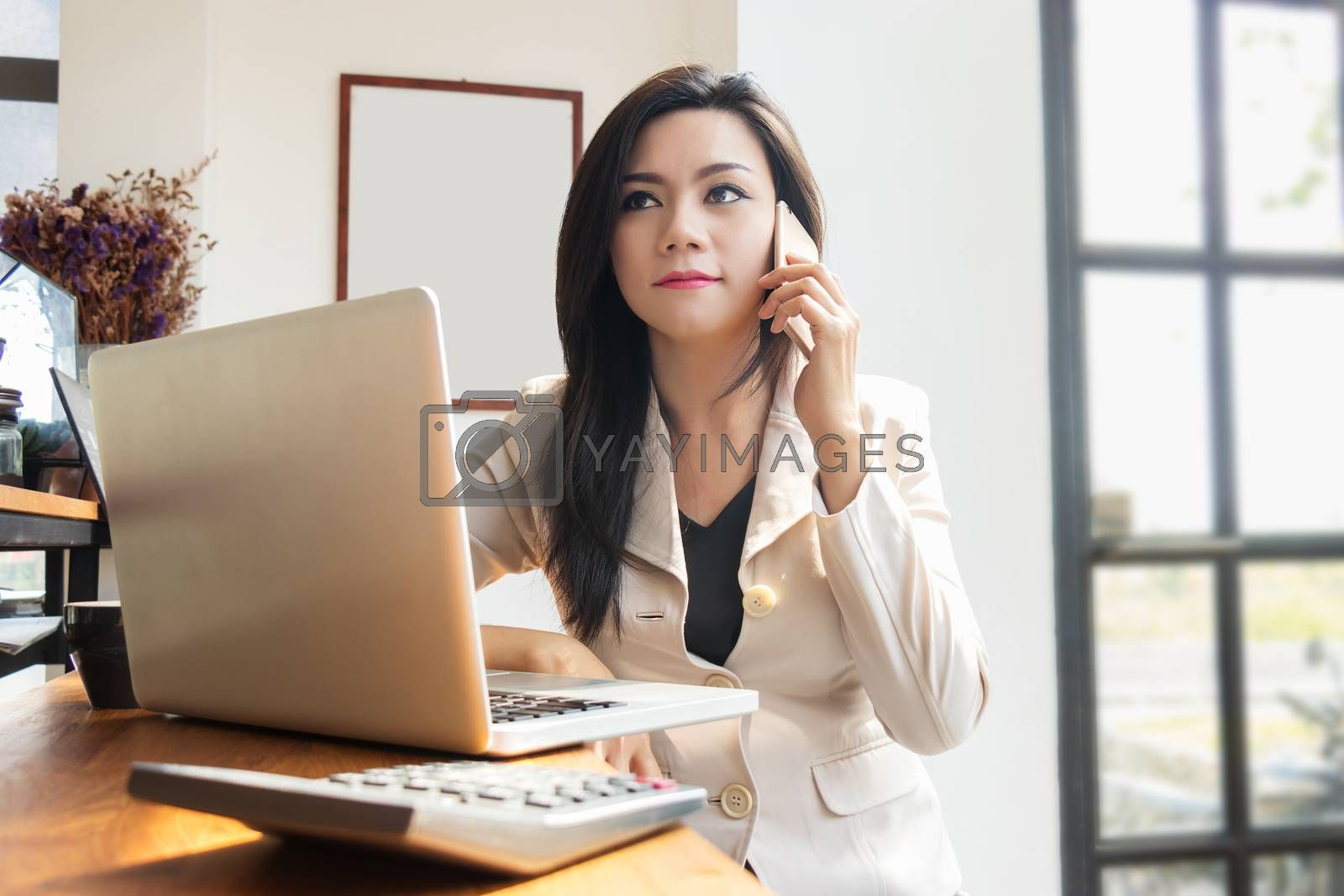Asian business woman working with laptop notebook and use mobile smartphone for contact communication with colleagues. implementation and coordination by using modern technology