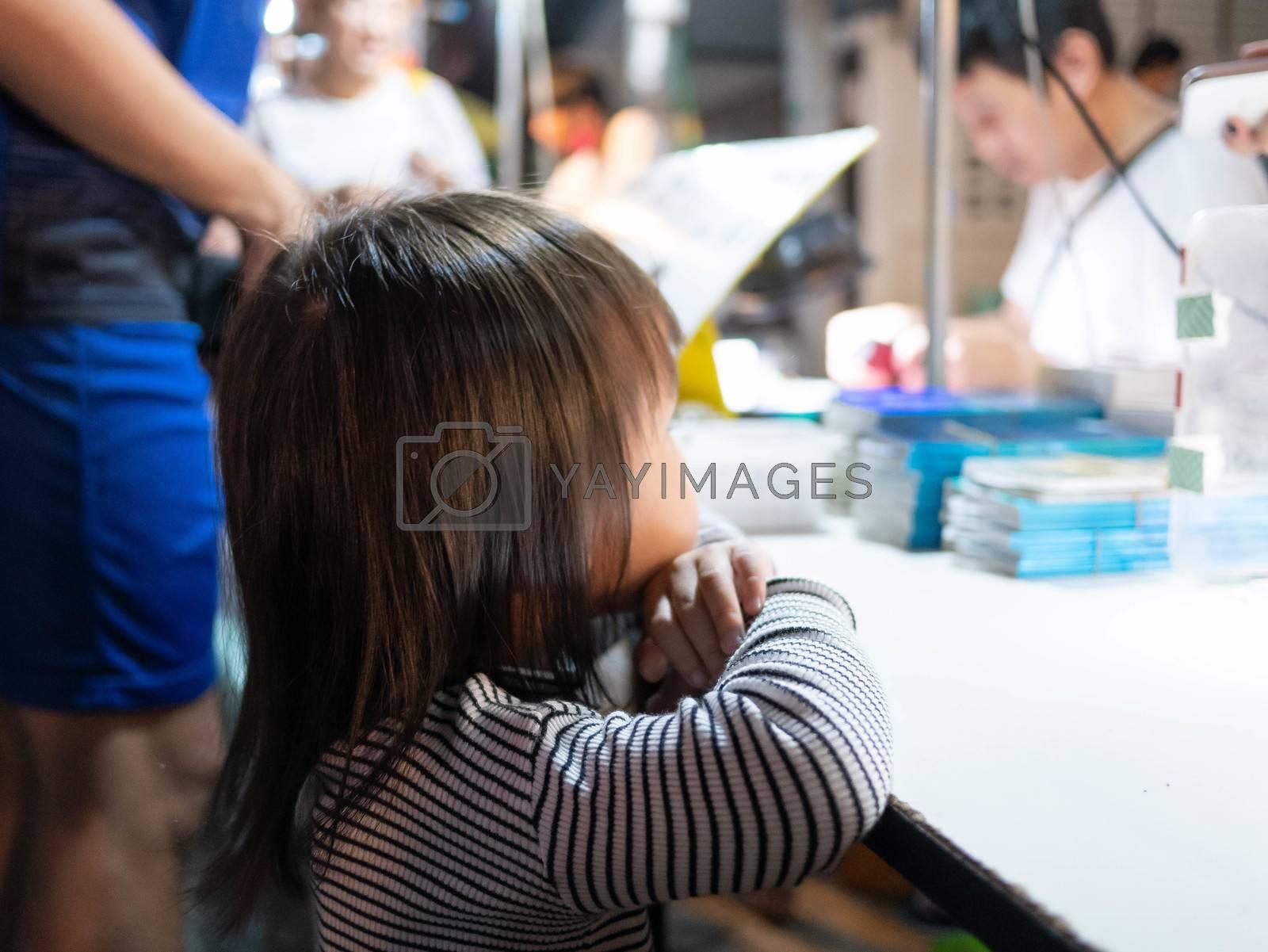 Lampang, Thailand; 5 October 2019 - Adorable Asian child girl stand to wait to buy foods at Kad Kong Ta Walking Street. by TEERASAK
