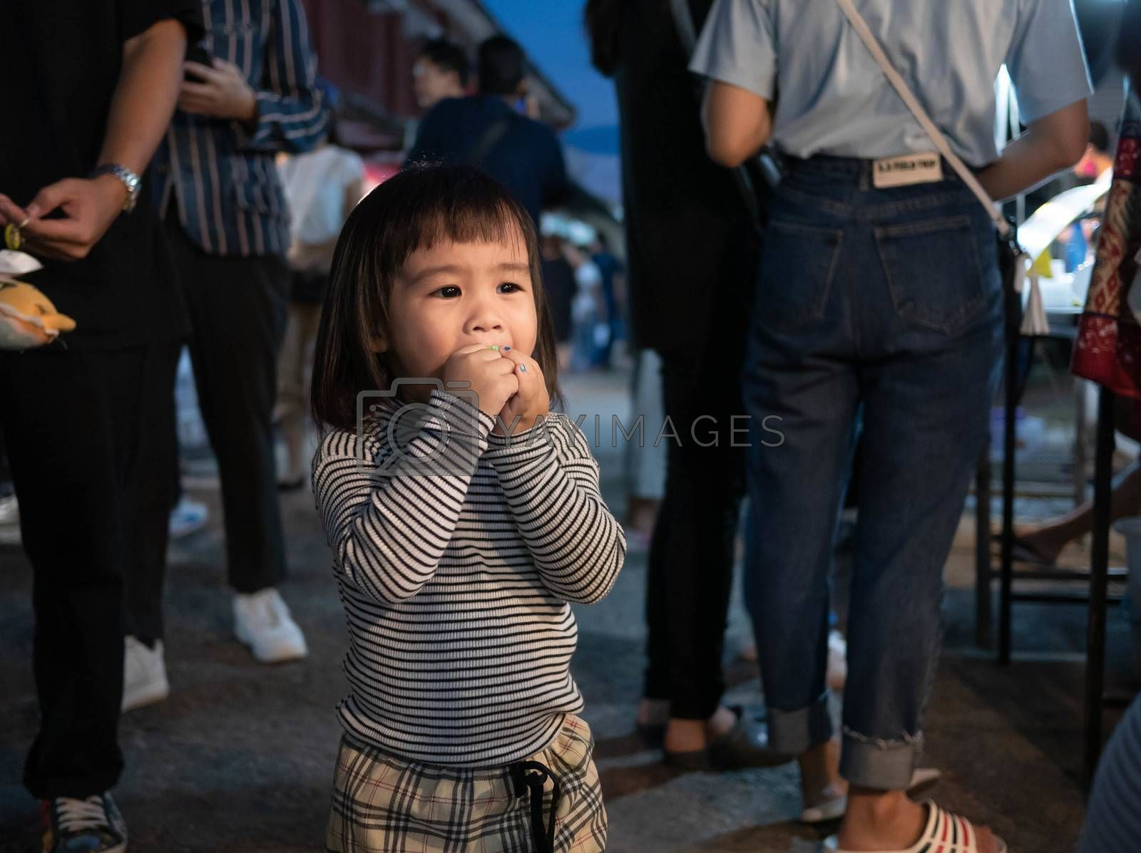 Lampang, Thailand; 5 October 2019 - Adorable Asian child girl having fun with Dracula teeth plastic toys in Kad Kong Ta Walking Street.