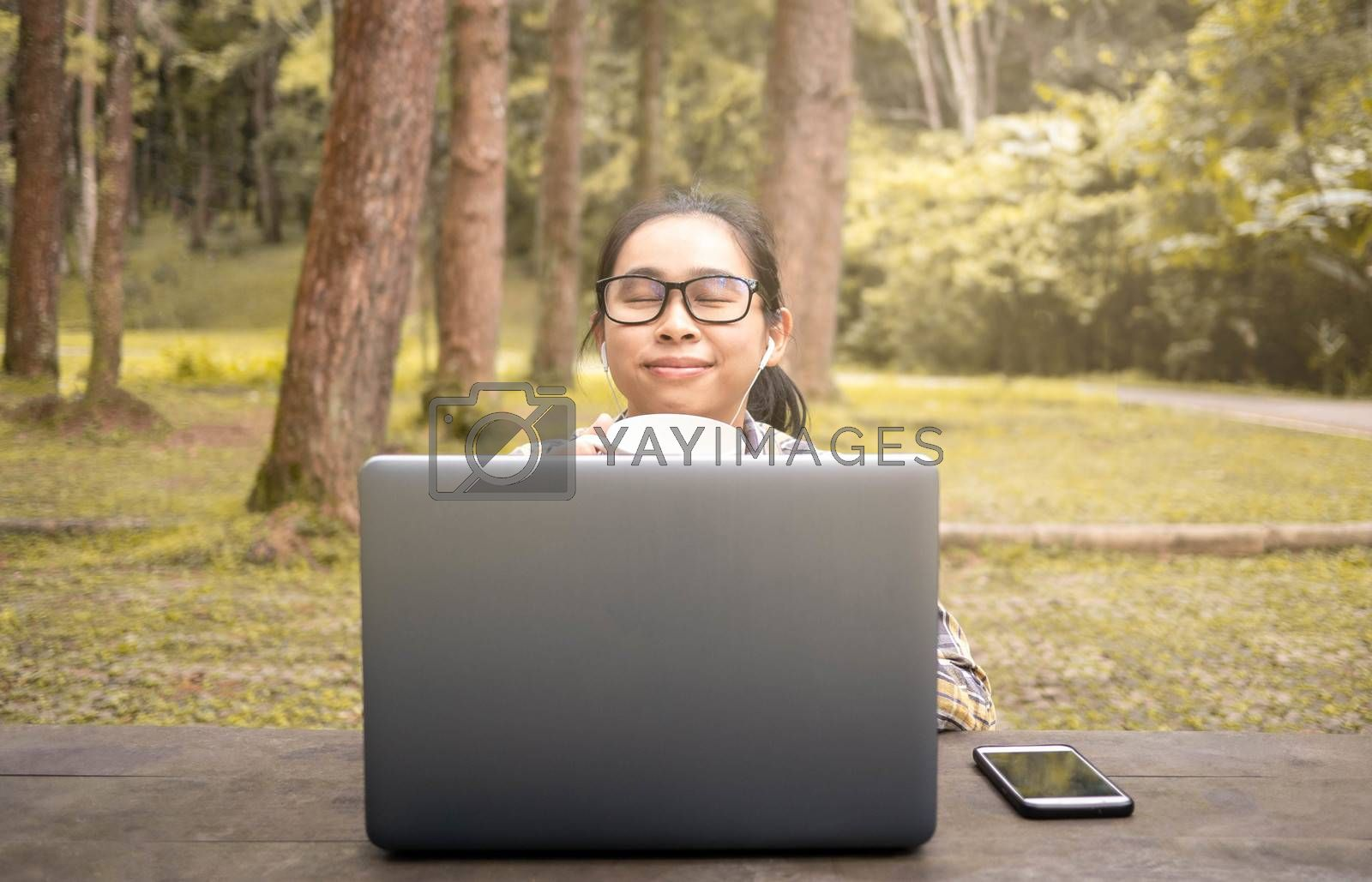 Happy casual beautiful woman working on laptop and drinking coffee while sitting in national park.