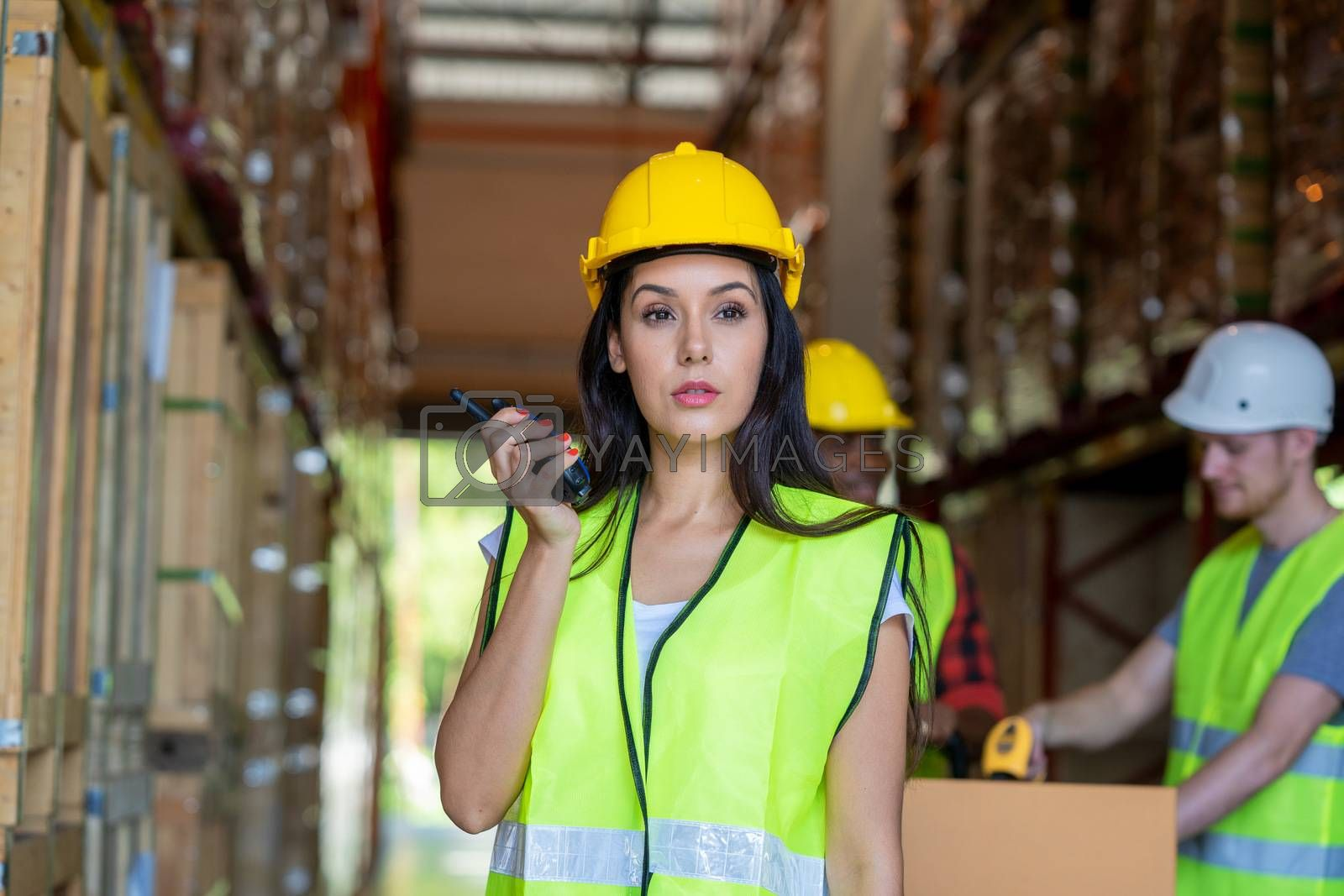 Warehouse worker using handheld radio receiver for communication by Visoot