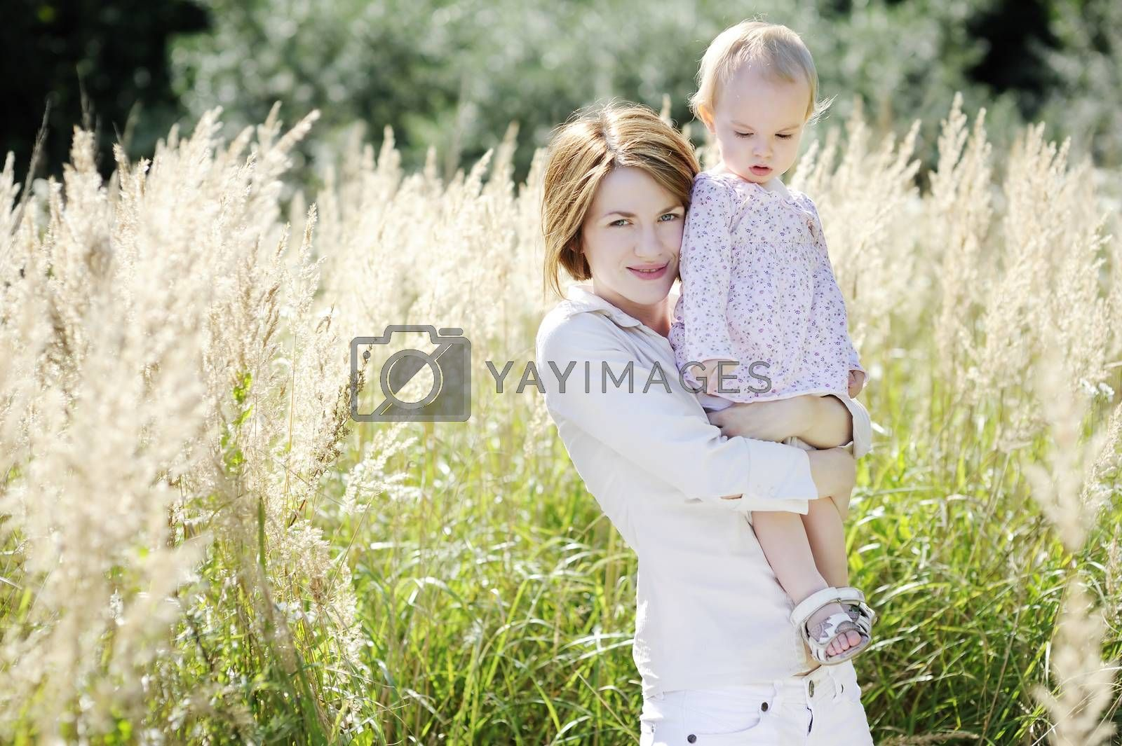 Young mother and her toddler girl in the grass