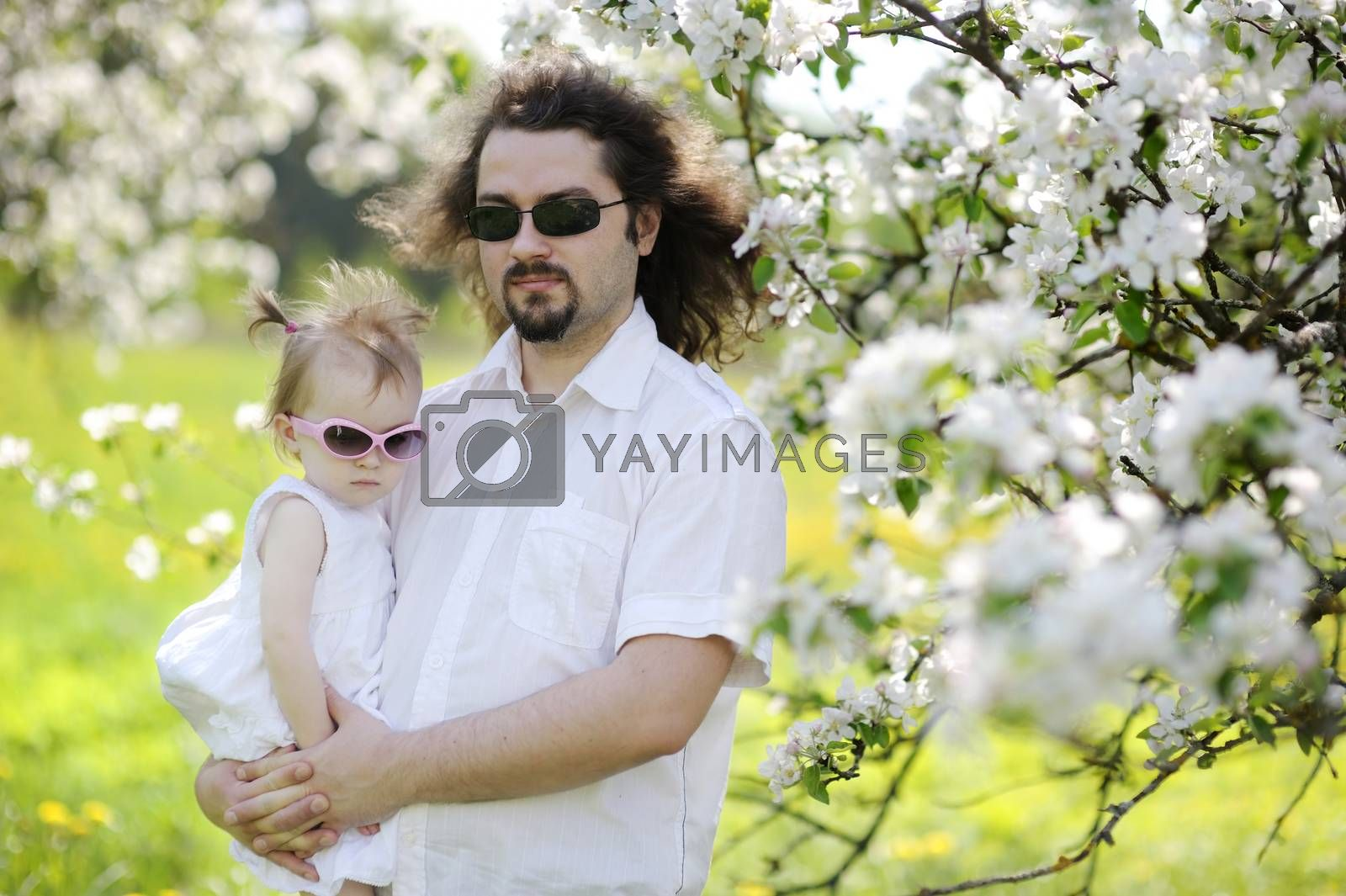 Young father and his daughter in blossoming trees