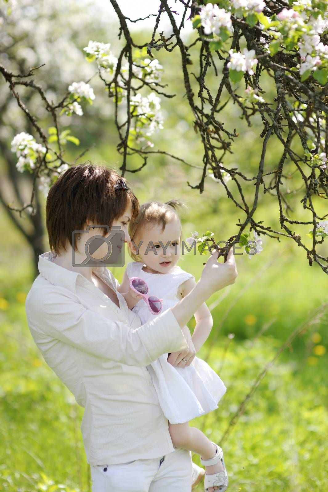 Young mother and her daughter in blossoming trees