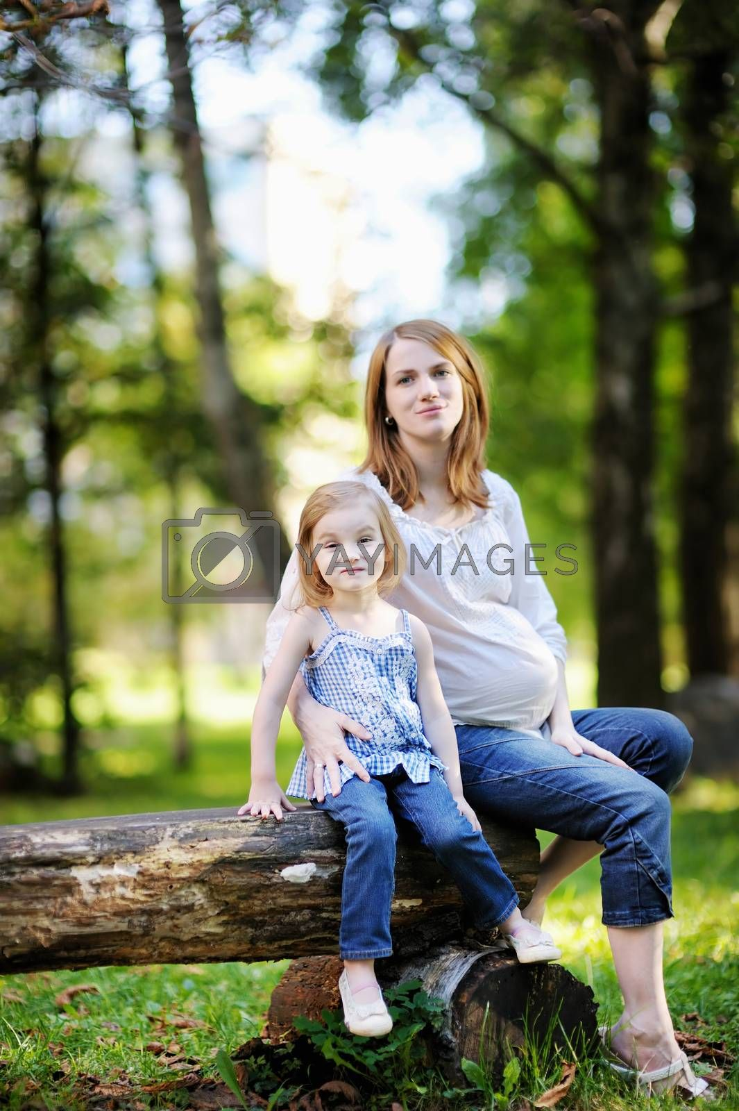 Little girl and her pregnant mother outdoors